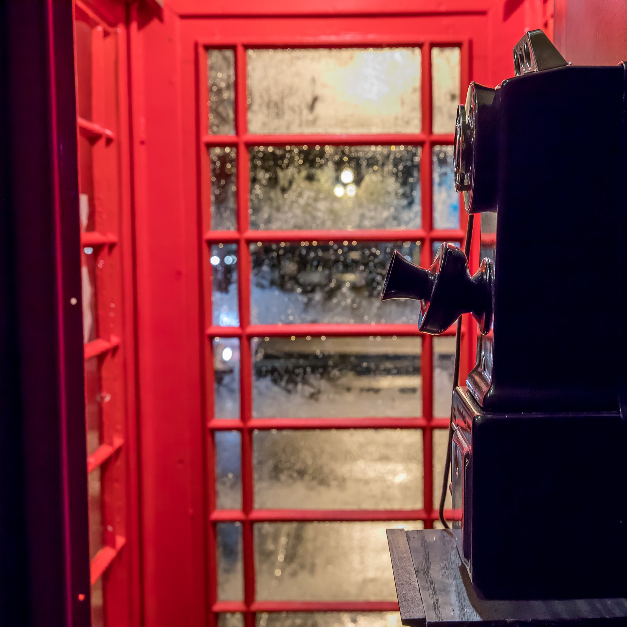 An old fashioned black telephone sits inside an red antique British phone booth as rain drops trickle down the closed glass door