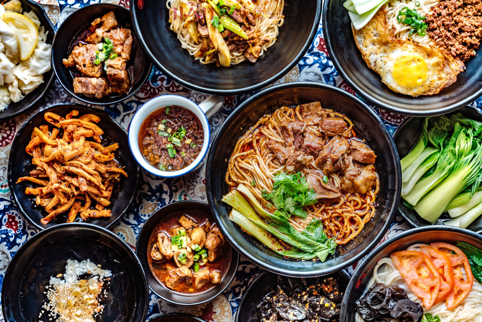 An overhead look at black bowls filled with noodles and other saucy items.