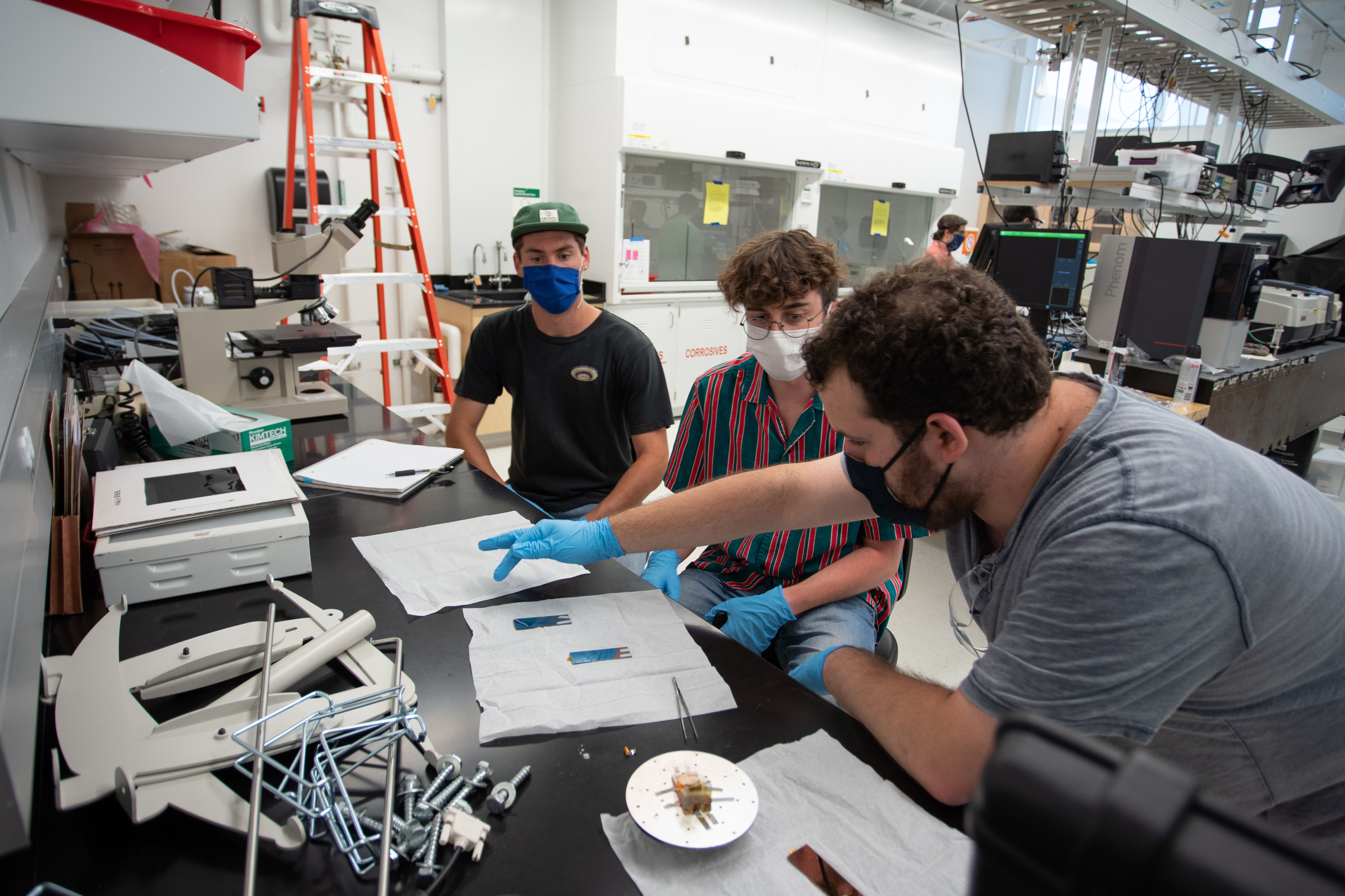 Three students wearing blue gloves gather around a work table in a lab class at the Colorado School of Mines. One student points at a paper.