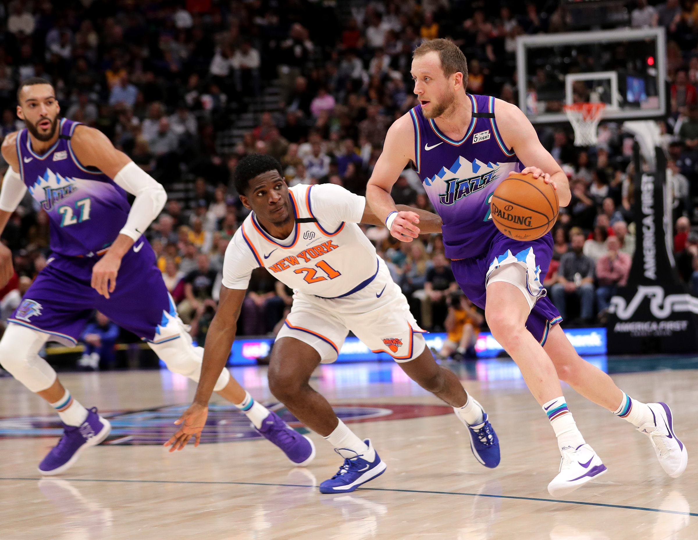 Joe Ingles drives around New York Knicks guard Damyean Dotson with Rudy Gobert trailing