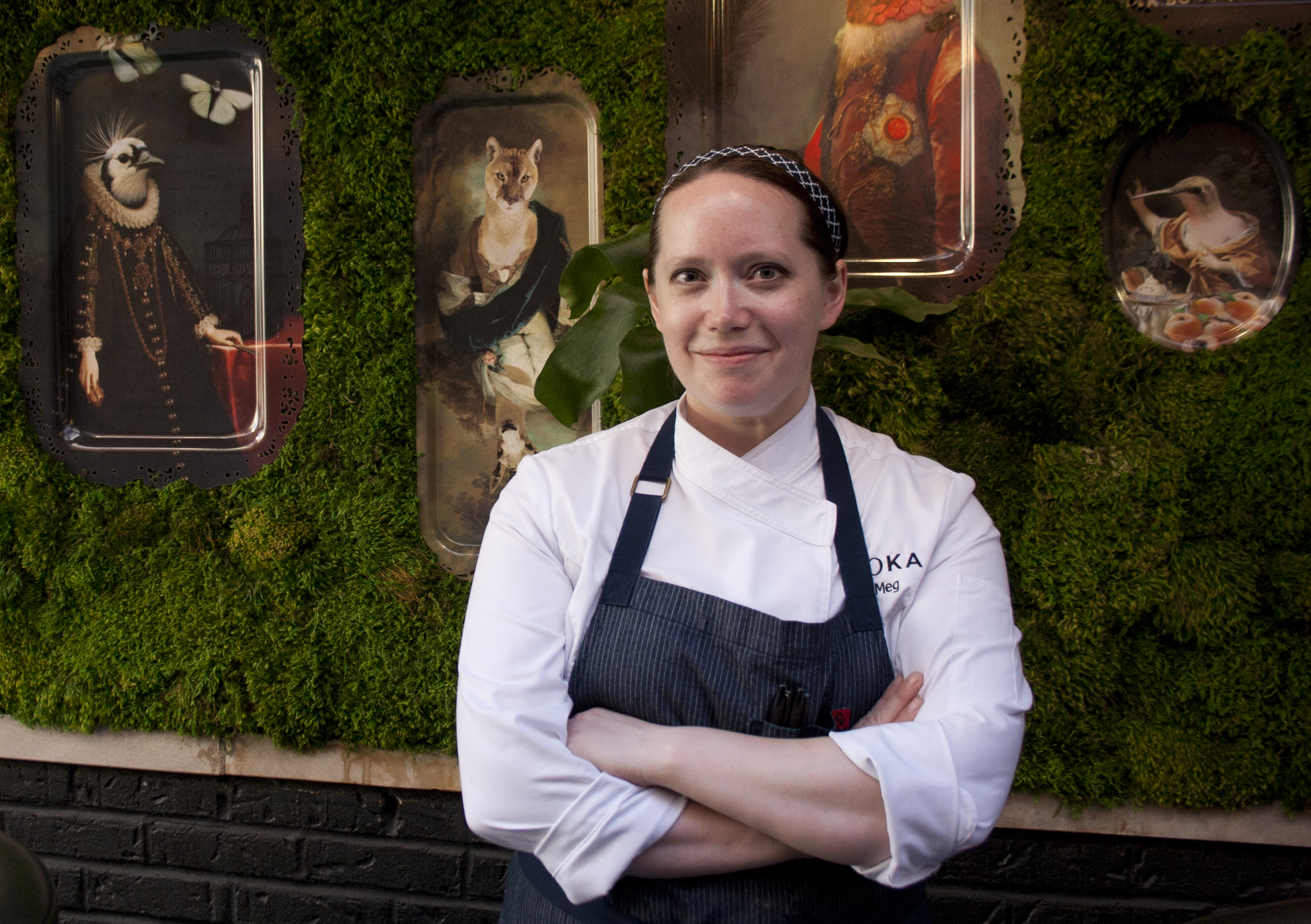 A smiling person with an apron in front of a turfed wall with framed art.