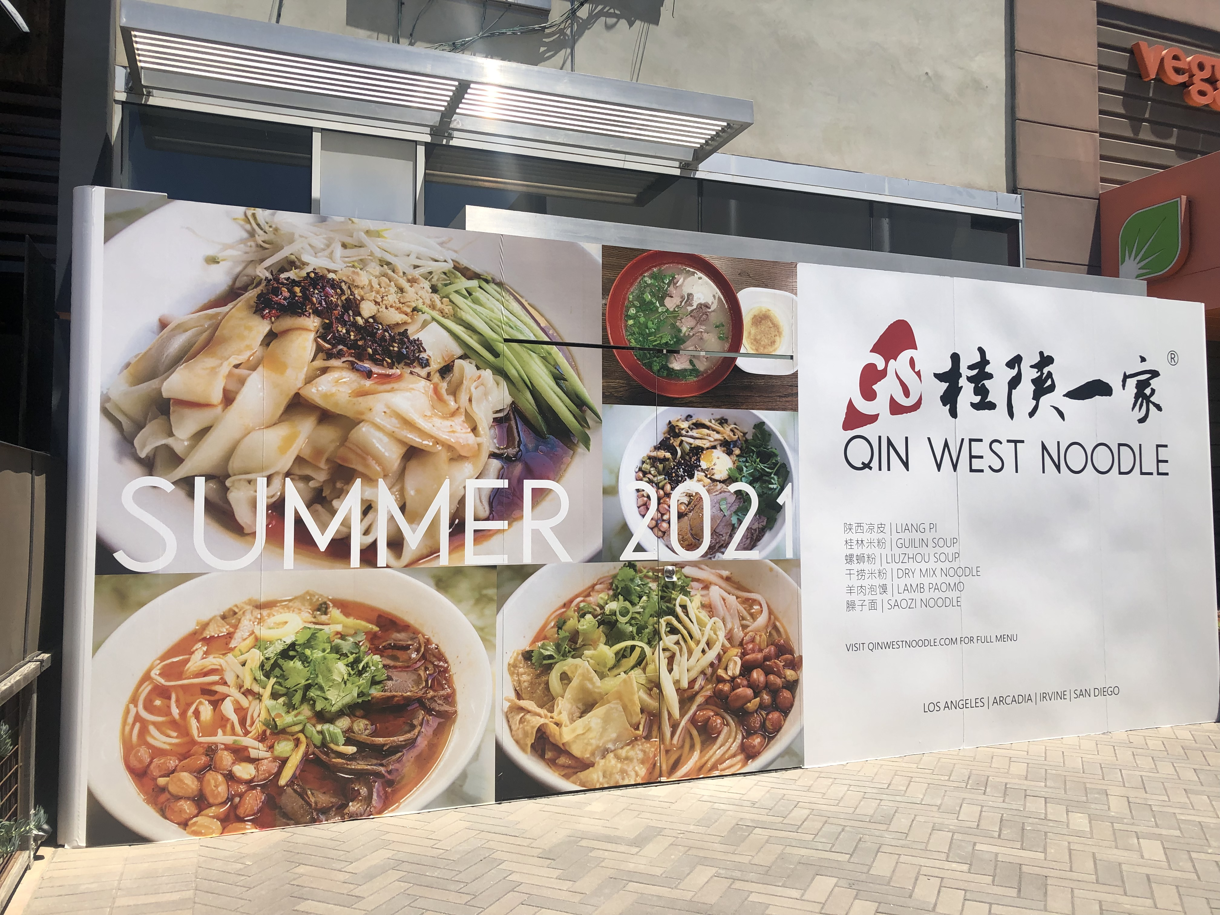 Temporary sign at Qin West Noodle lists Summer 2021 opening