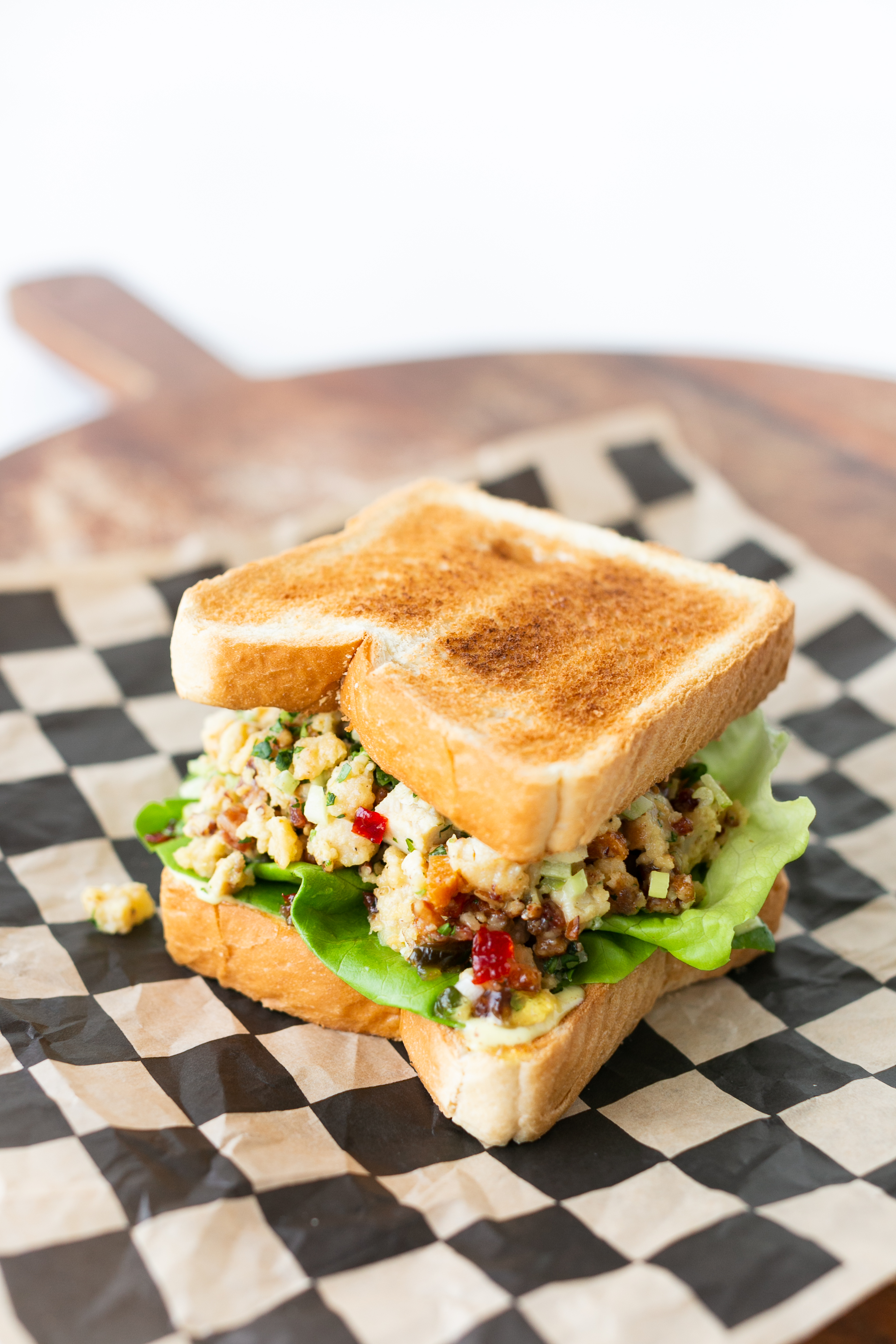 A sandwich with sliced white bread and chicken salad on top of a black-and-white checkered food wrapper liner