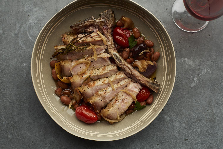 Tamworth pork chop with apricot glaze, confit garlic, and borlotti beans