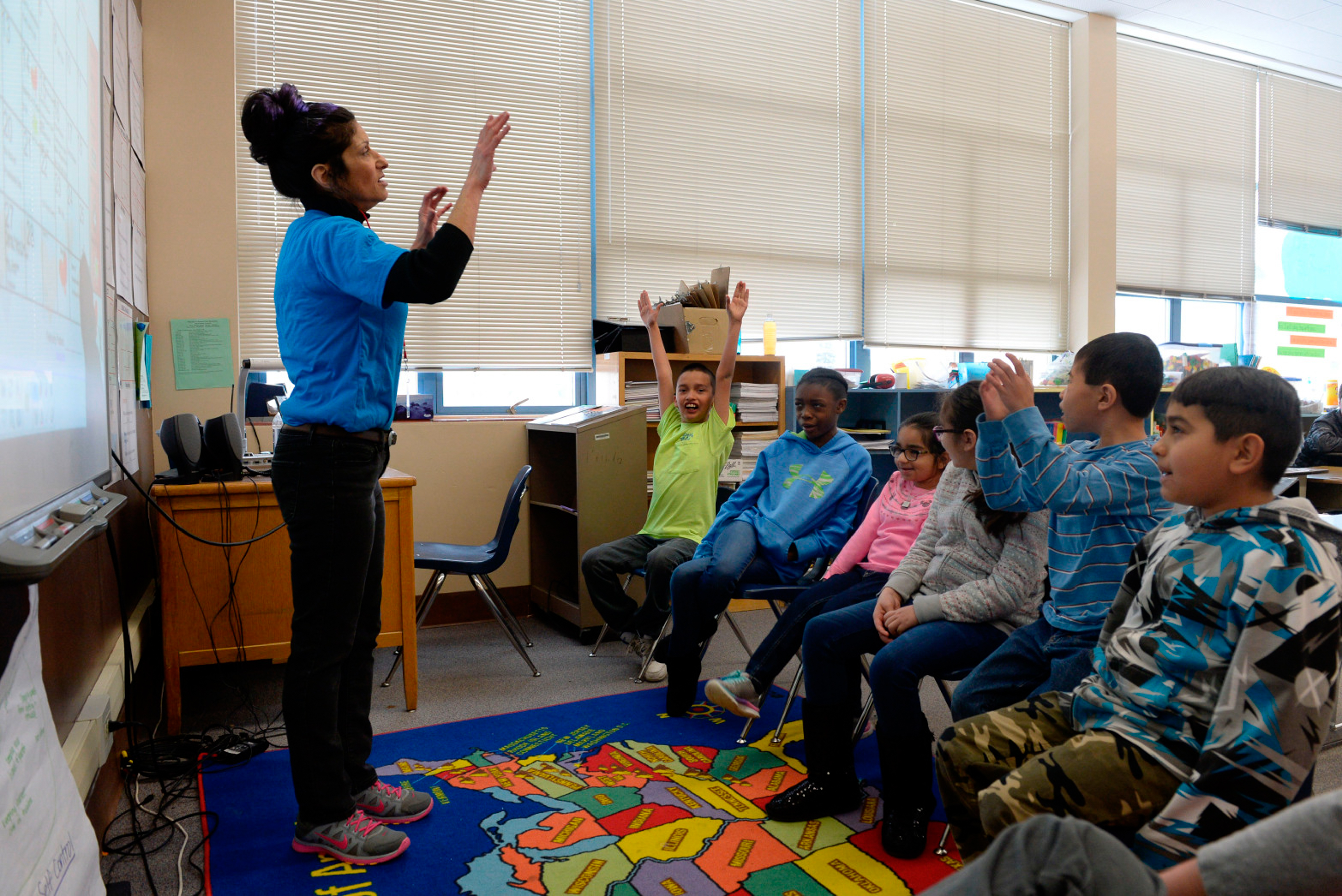 A group of six elementary students sit together and engage with their teacher, standing at the front of the classroom with her arms raised.