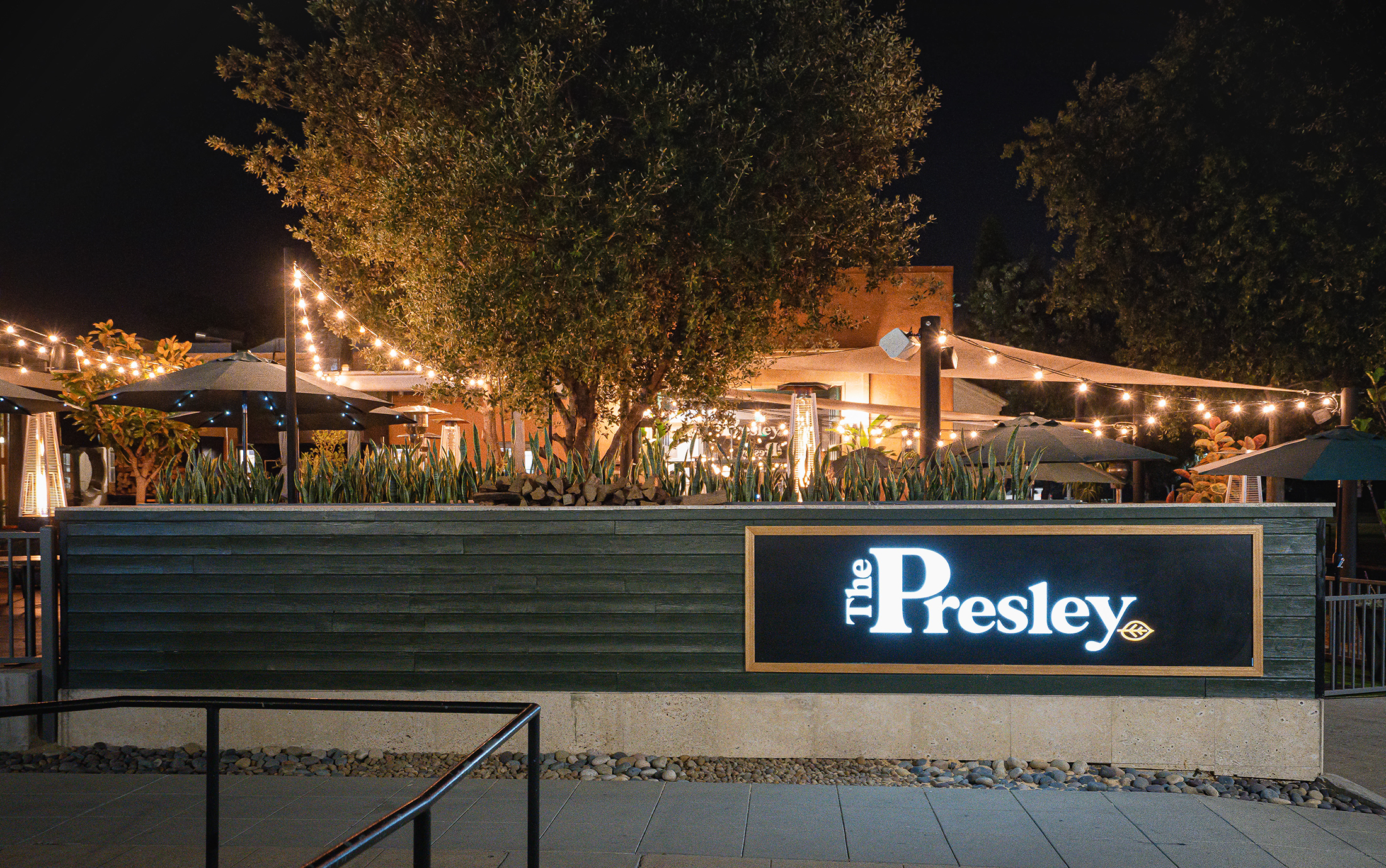 Front patio with lights and umbrella tables at The Presley in Liberty Station
