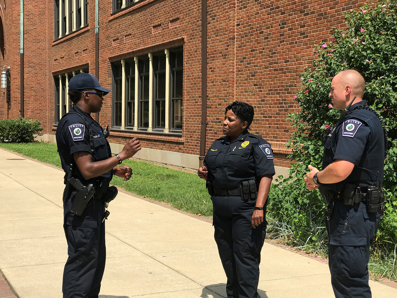 Indianapolis Public Schools Police Department Chief Tonia Guynn talks to two other officers working for the district in front of a school building.