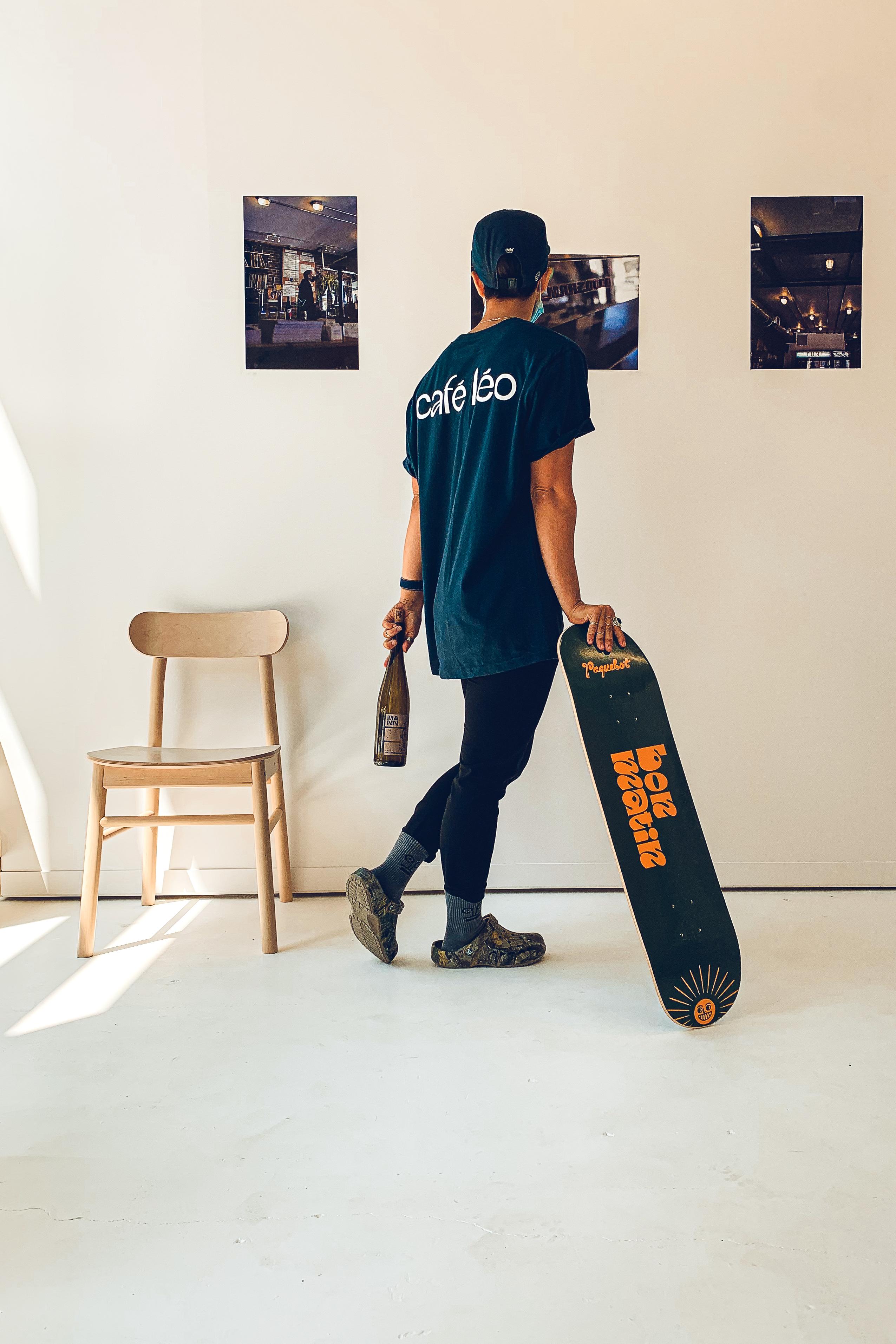 guy holding skateboard looking at photos