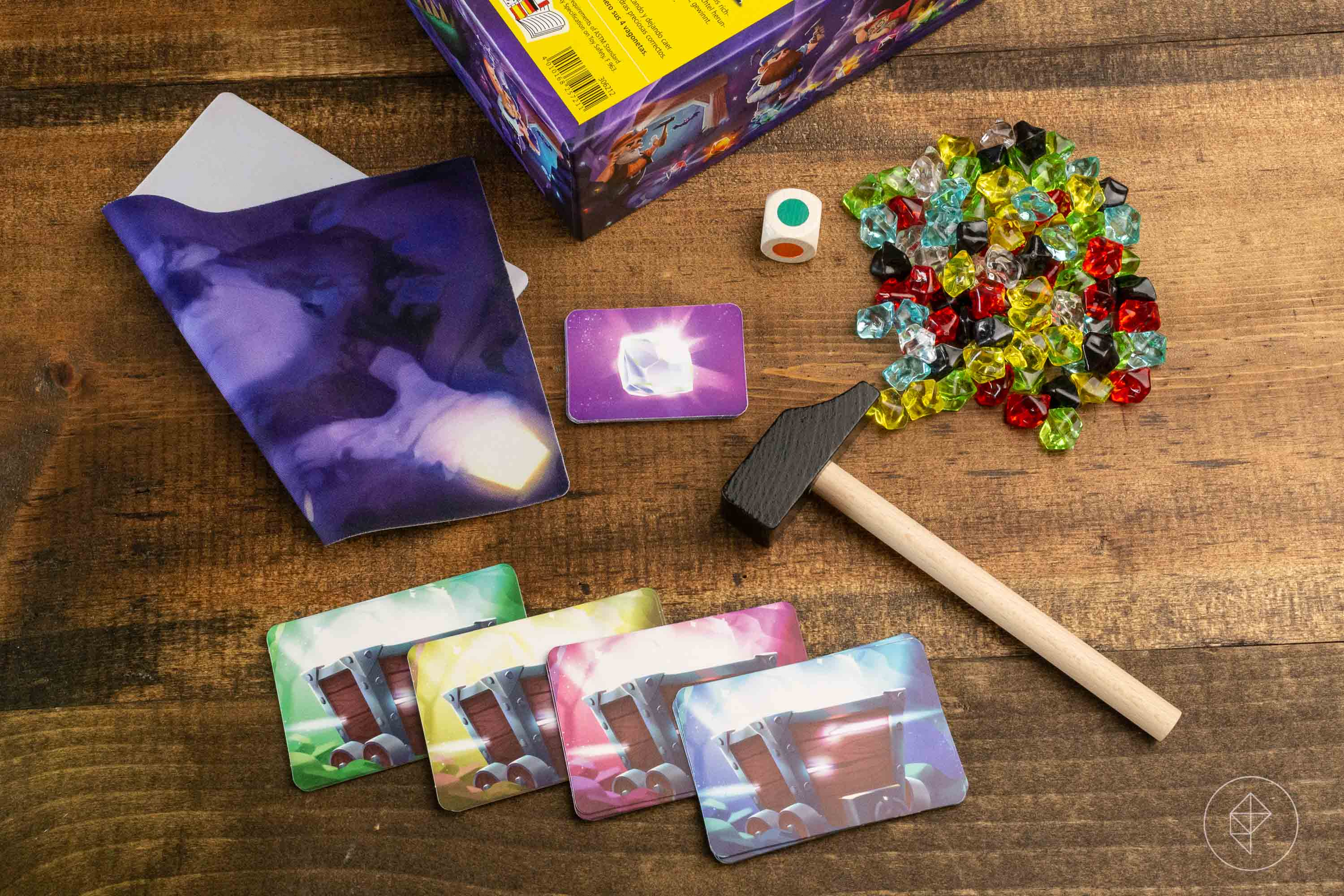 A small wooden hammer, with cards, dice, and plastic gems sitting on a table.