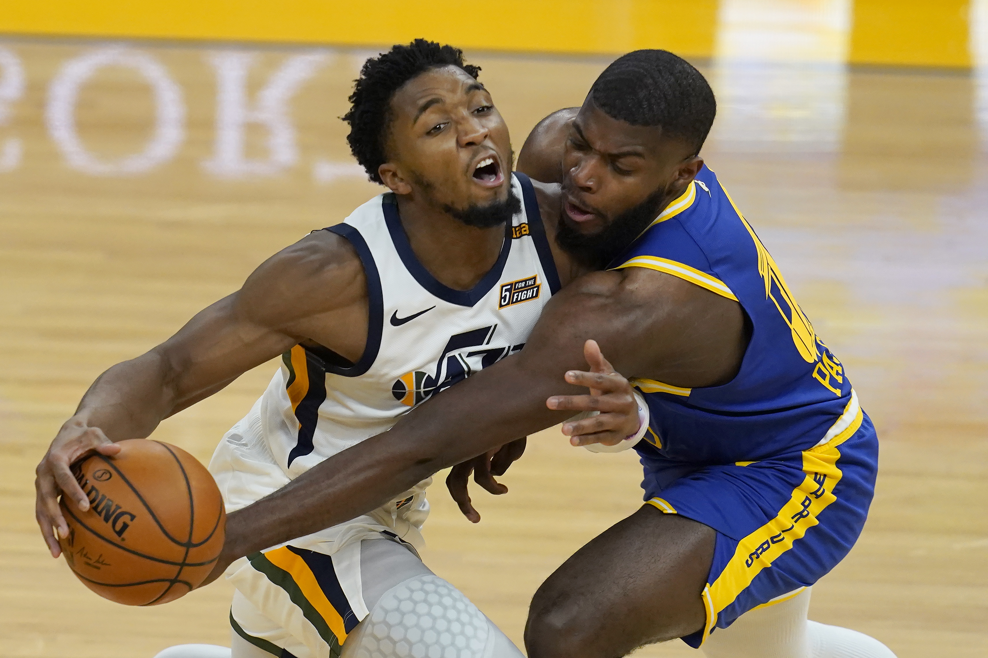 Utah Jazz guard Donovan Mitchell, left, is defended by Golden State Warriors forward Eric Paschall, right