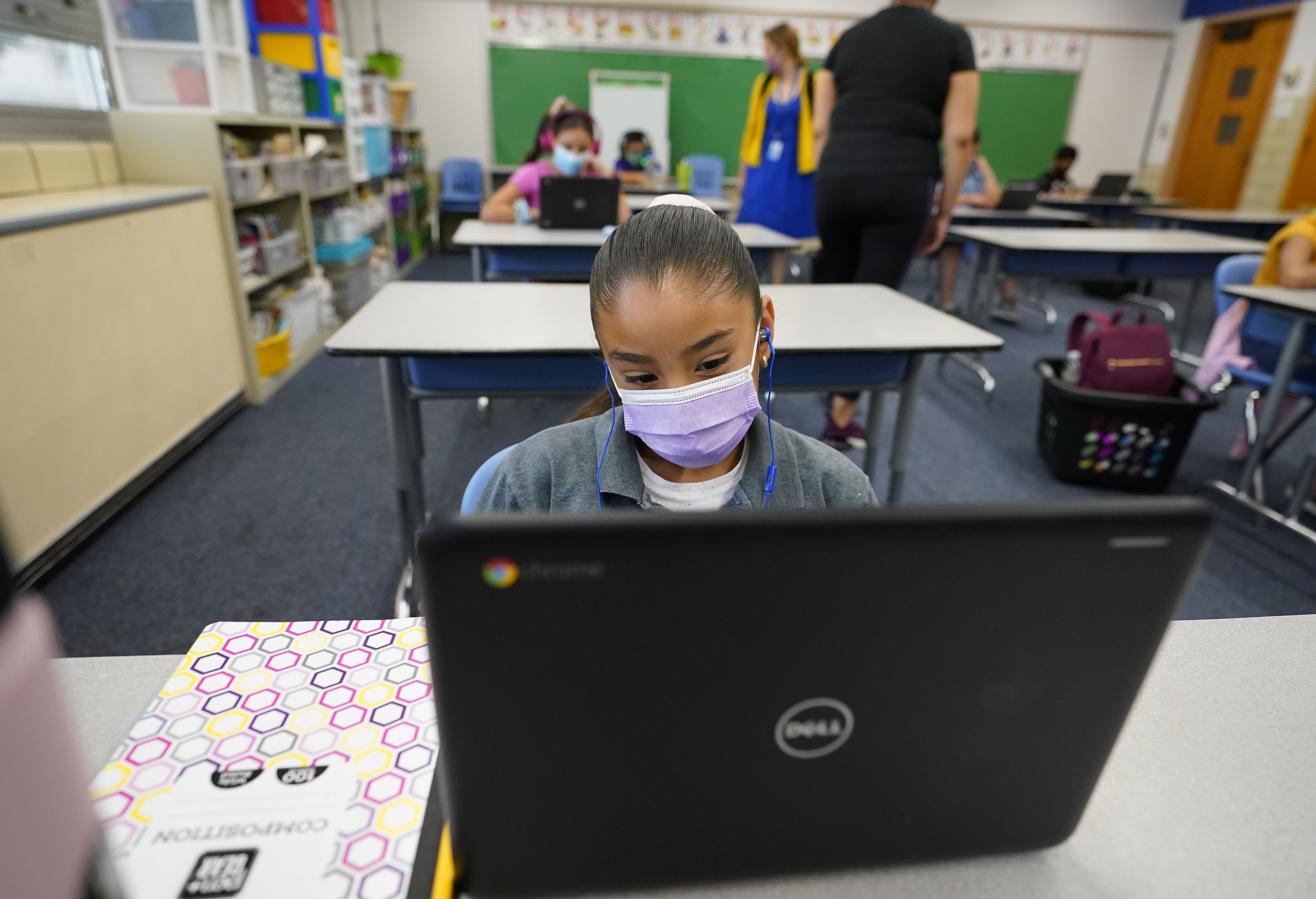 A masked girl works on her laptop at a learning center.
