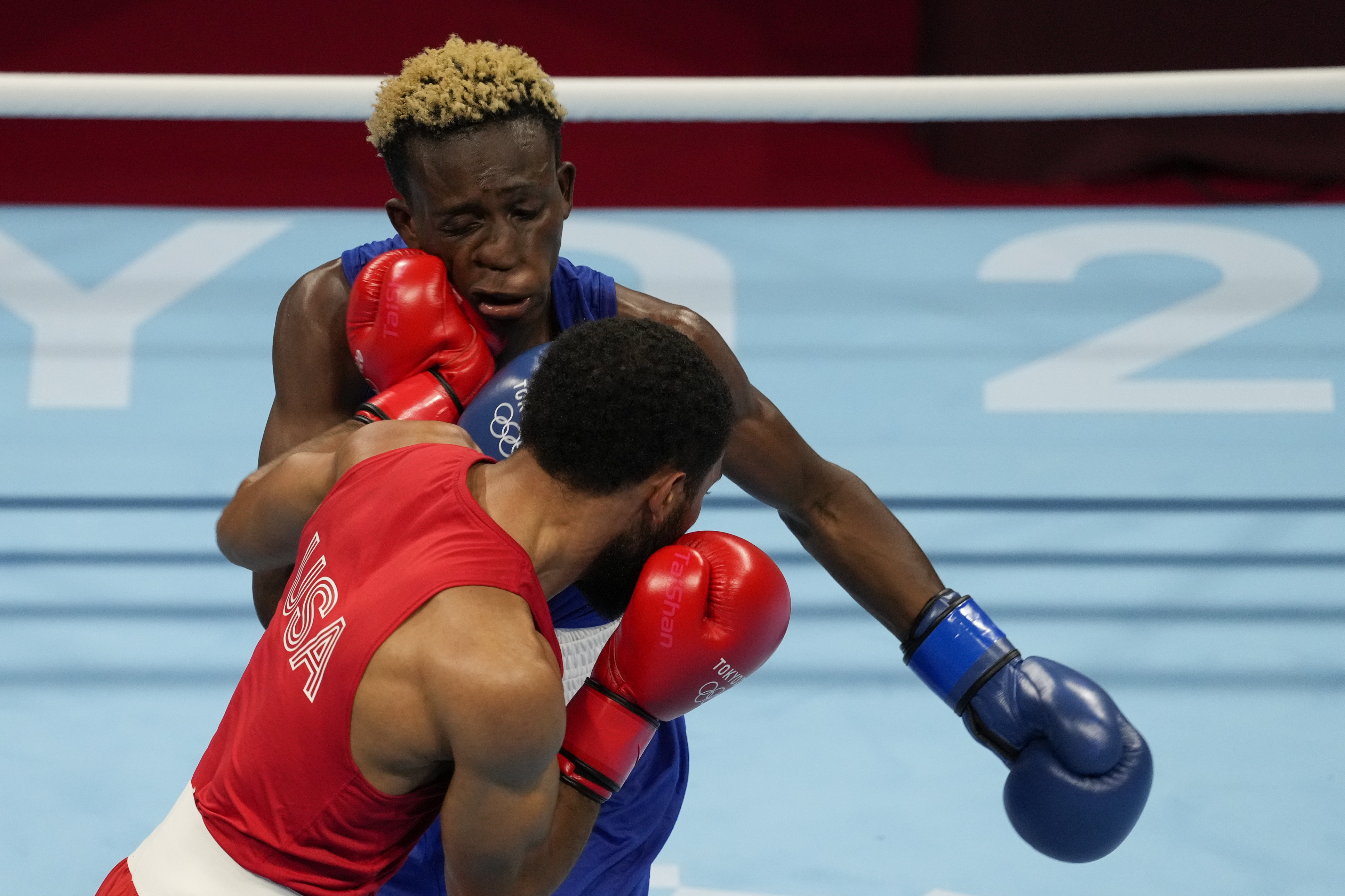 Duke Ragan (USA) in red and Samuel Takyi (GHA) in blue fight in their semifinal Men's Featherweight class during the Tokyo 2020 Olympic Summer Games at Kokugikan Arena.