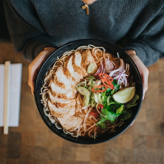 A person holds a large black bowl of ramen with topped with herbs and lined with a semi circle of pork belly slices from Wagamama