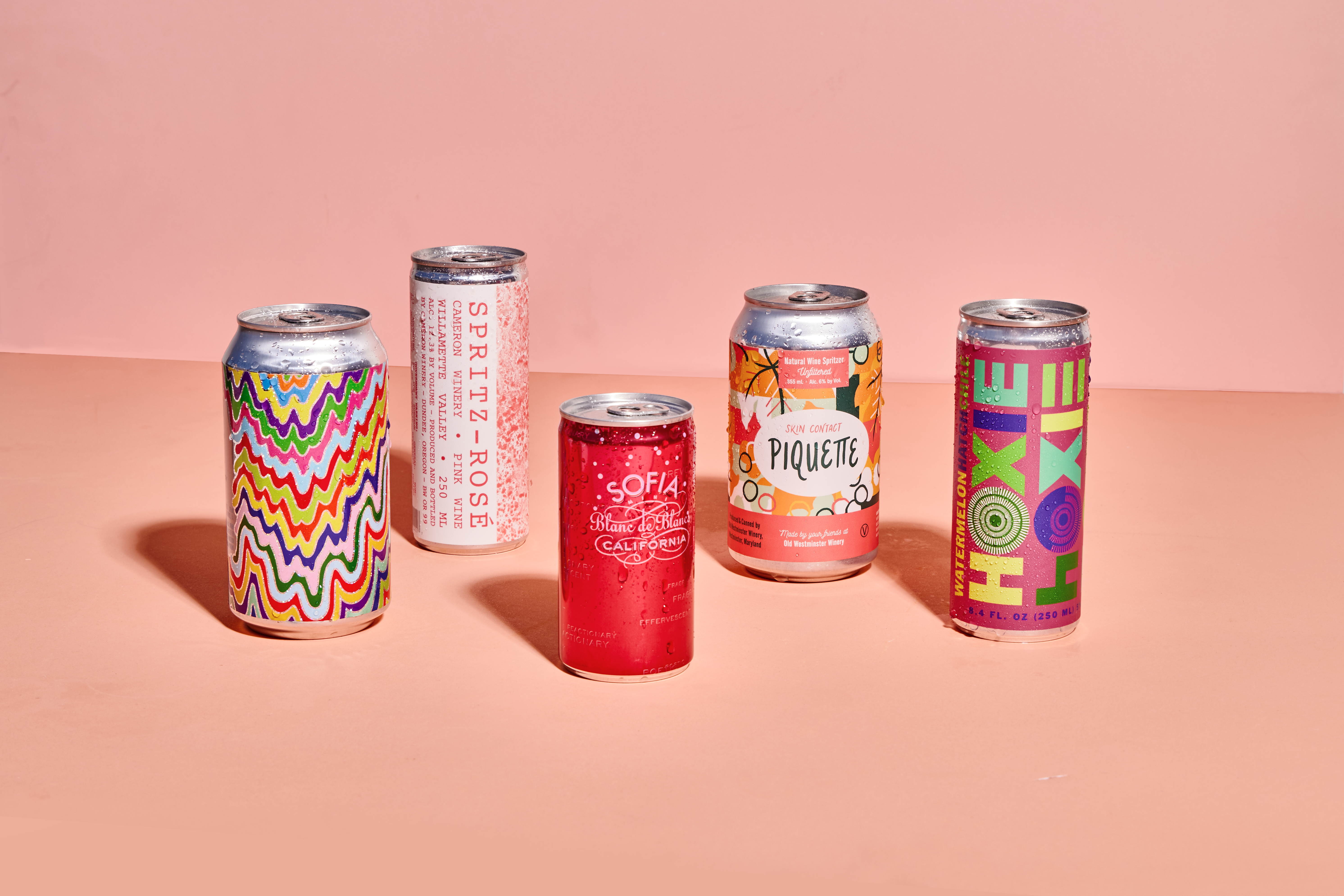 Five colorful cans on a pink background.