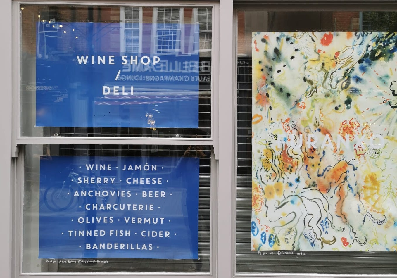 A grey window frame with decals advertising Furanxo, a wine shop and deli
