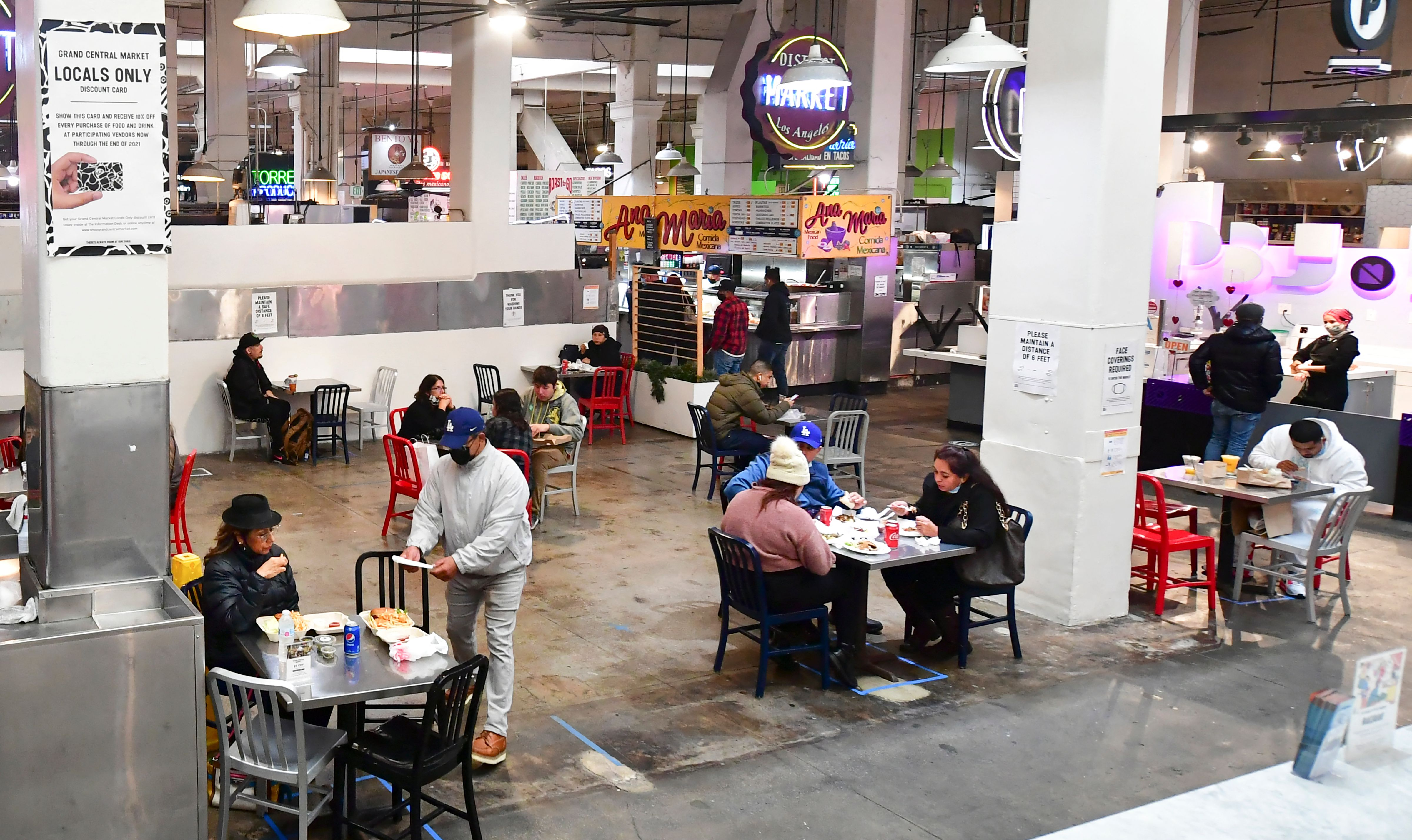 People enjoy lunch at Grand Central Market as indoor dining reopens in Los Angeles, on March 15, 2021.