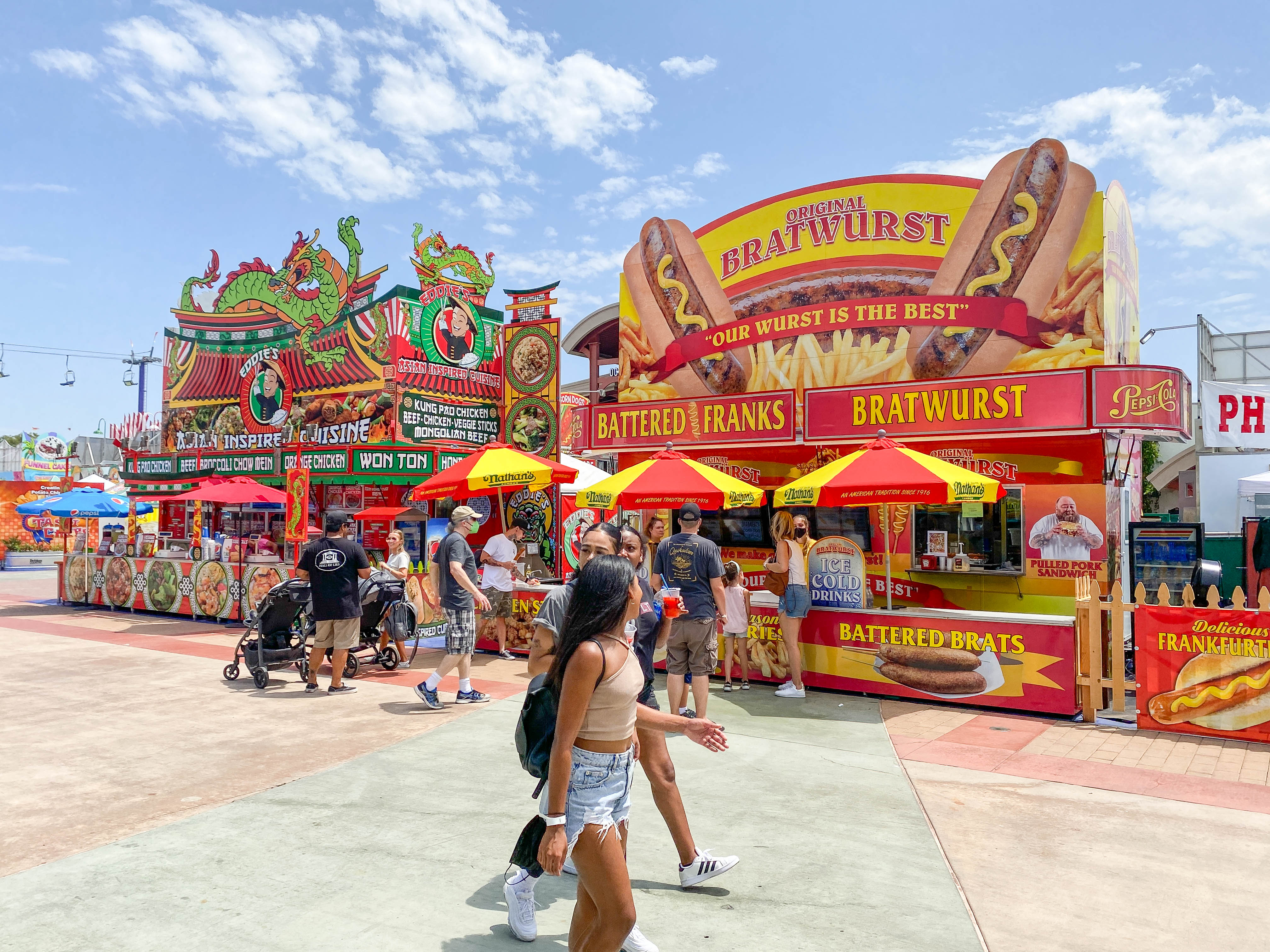 A crowd passes by a bright food stand at an open-air fair.