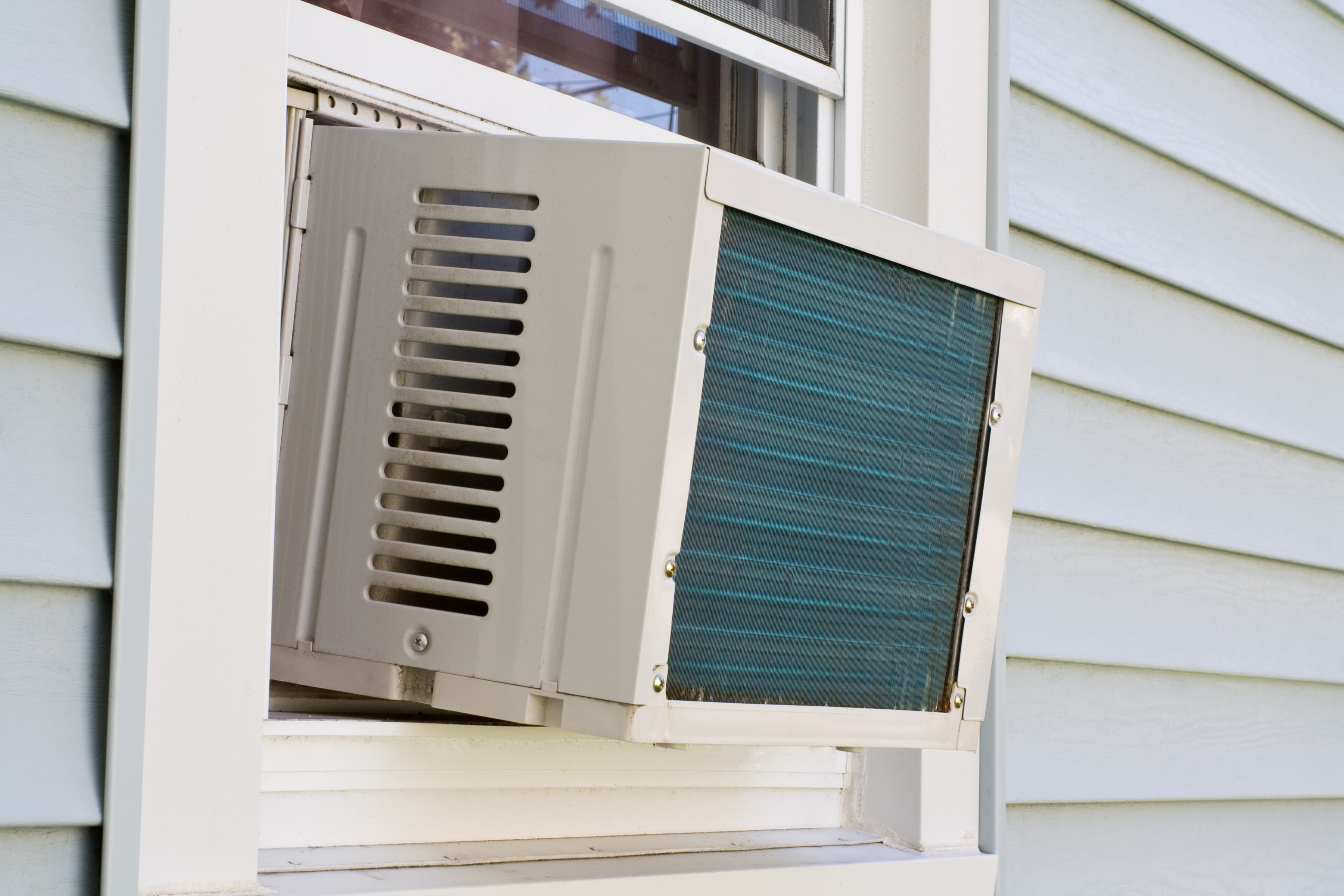 The exterior of a house with a brand new AC unit in the window.