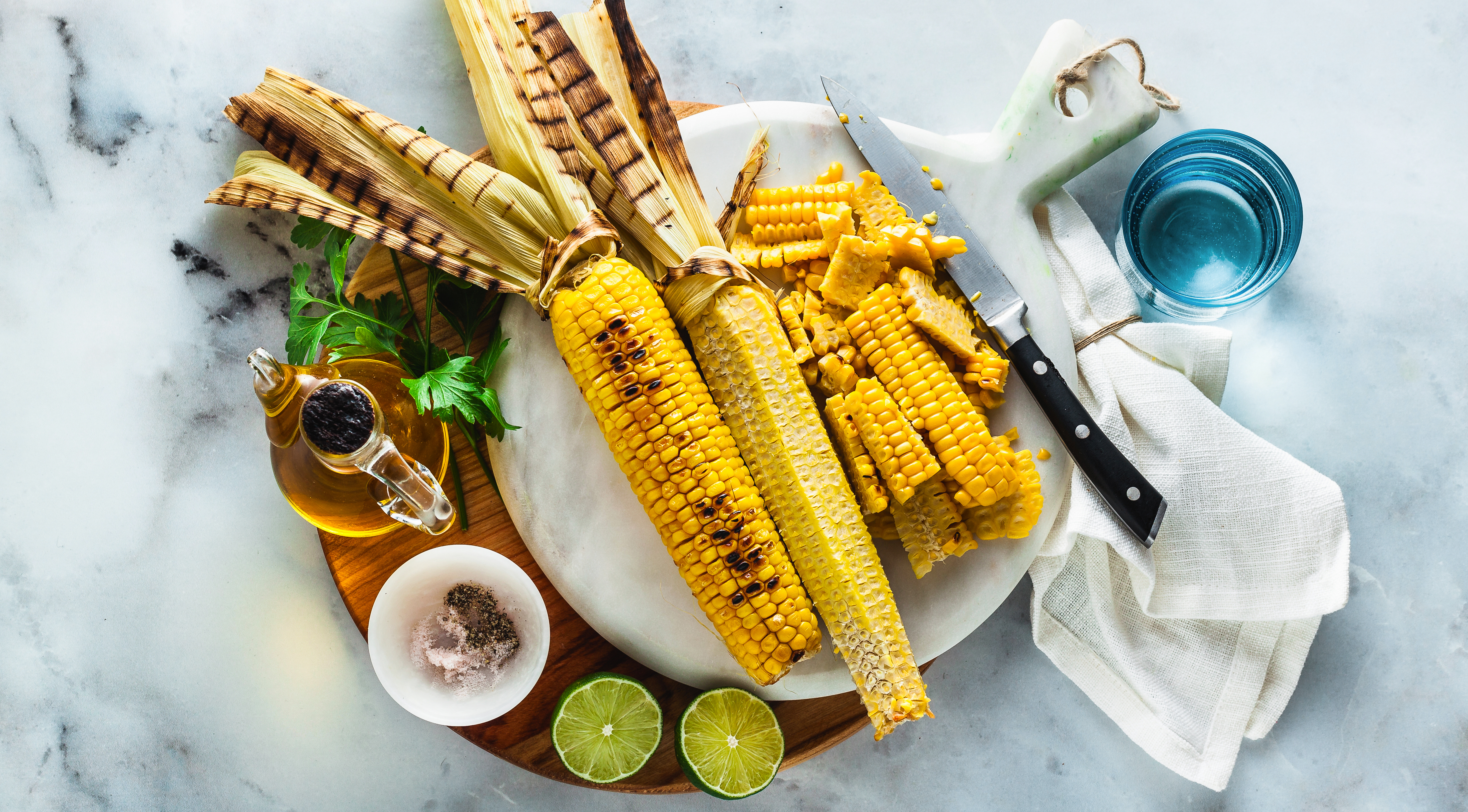 A plate of grilled corn on the cob surrounded by cut off wedges of kernels, limes, oil, and a blue glass on a white marble table top.