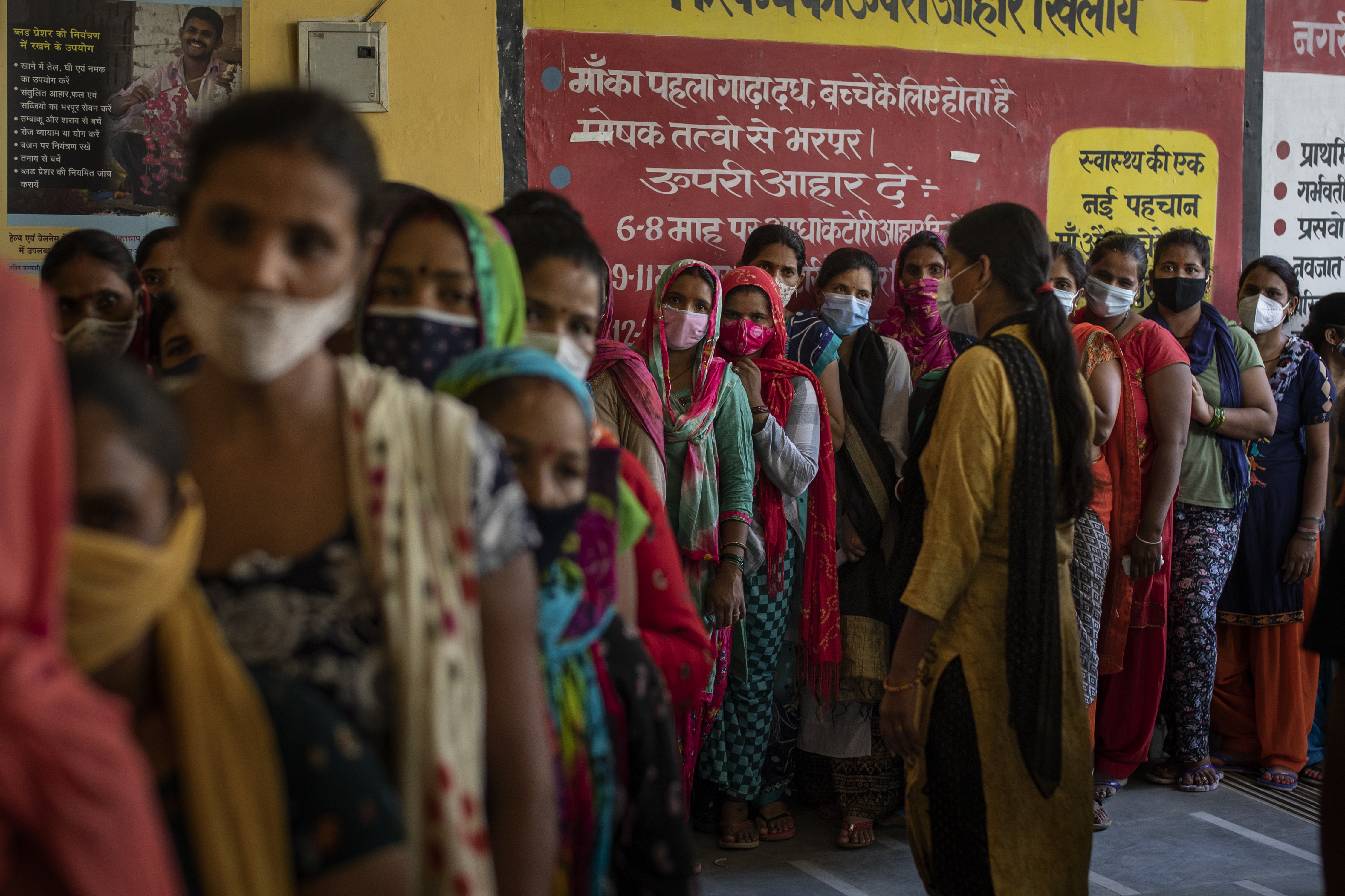 People wait in line for the arrival of vaccines during a vaccination drive against the coronavirus at a government health centre in Noida, a suburb of New Delhi, India,