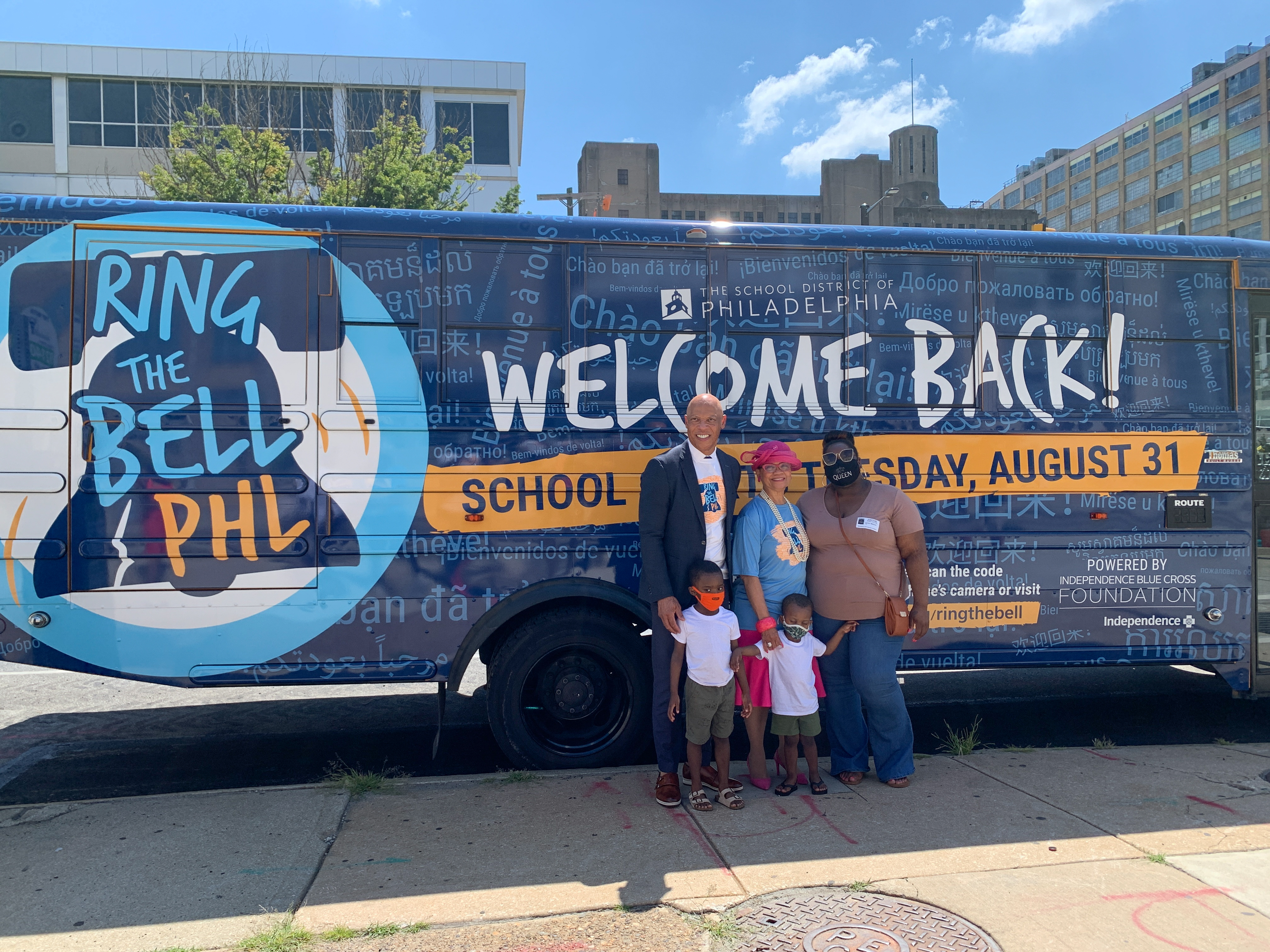"""Philadelphia Superintendent William Hite stands in front of a large bus that reads """"Ring the Bell PHL, Welcome Back!"""" with two women and two young boys."""
