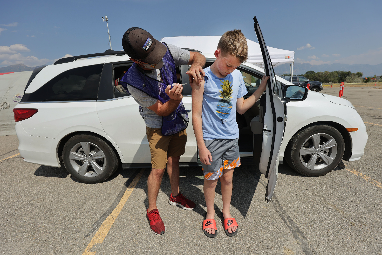 Utah Air National Guard Cpt. Raymond Searles gives Hamilton Barney, 13, COVID-19 vaccine during a Utah County Health clinic at Equestrian Park in Highland on Thursday, Aug. 5, 2021.