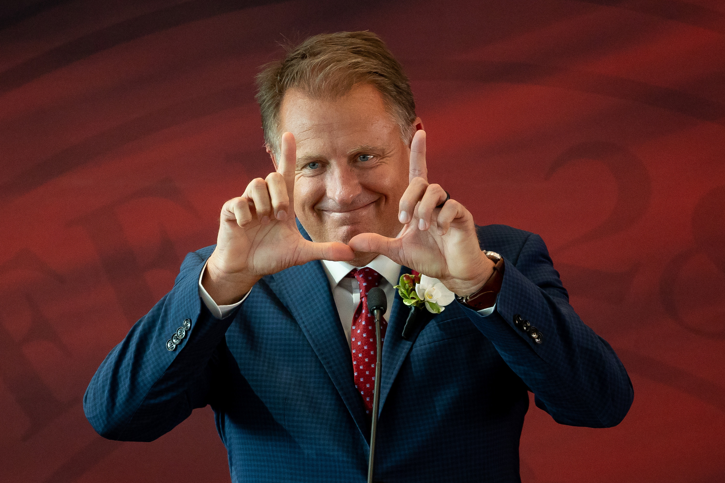 """Taylor R. Randall flashes a """"U"""" after being named the next president of the University of Utah at Rice-Eccles Stadium in Salt Lake City on Thursday, Aug. 5, 2021."""