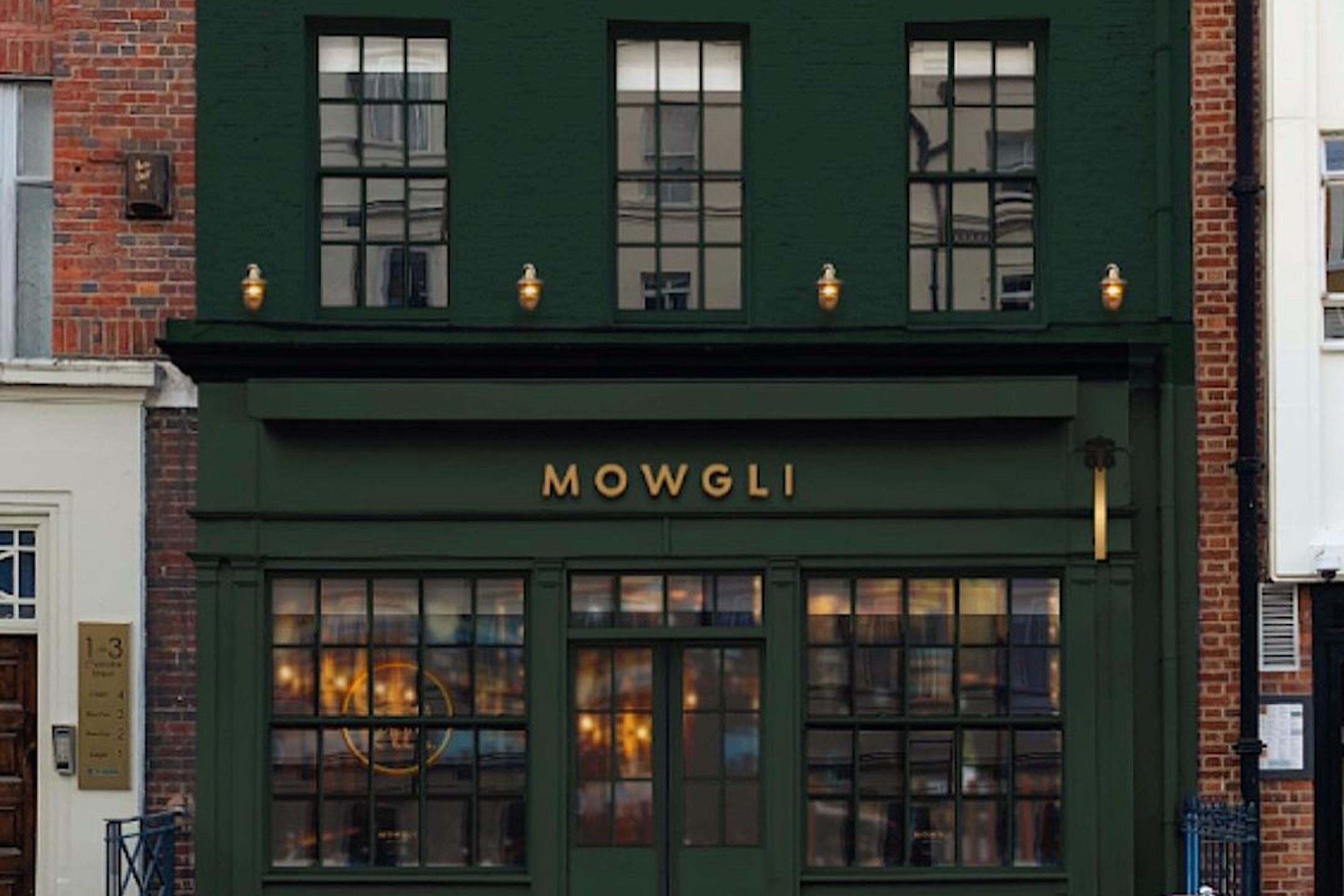 """A rendering of the upcoming Mowgli restaurant on Charlotte Street in Fitzrovia, with a dark green frontage and awning and """"Mowgli"""" written in capital letters and gold type"""