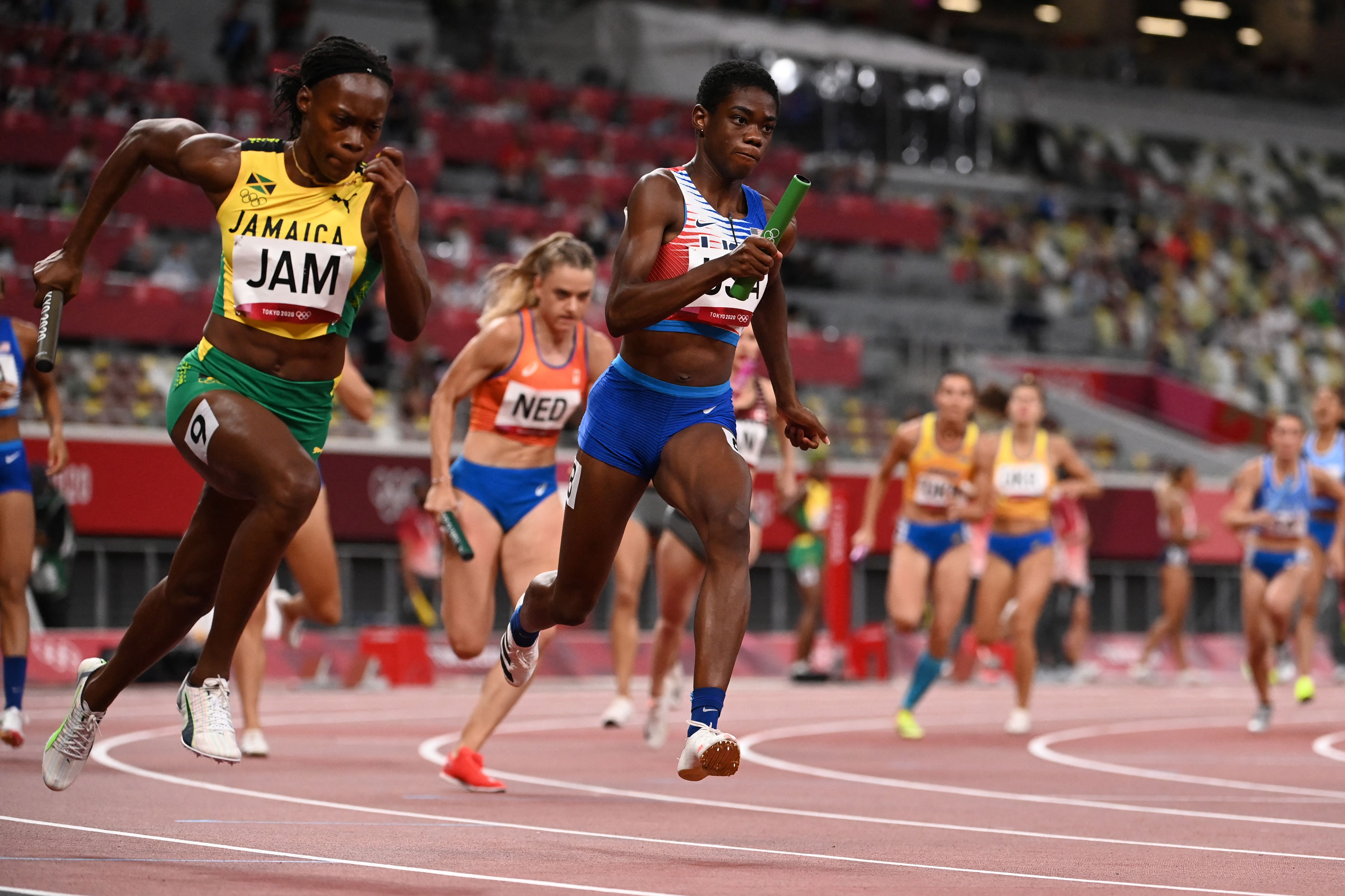 Jamaica's Roneisha McGregor (L) and USA's Wadeline Jonathas compete in the women's 4x100m relay heats during the Tokyo 2020 Olympic Games at the Olympic Stadium in Tokyo on August 5, 2021.