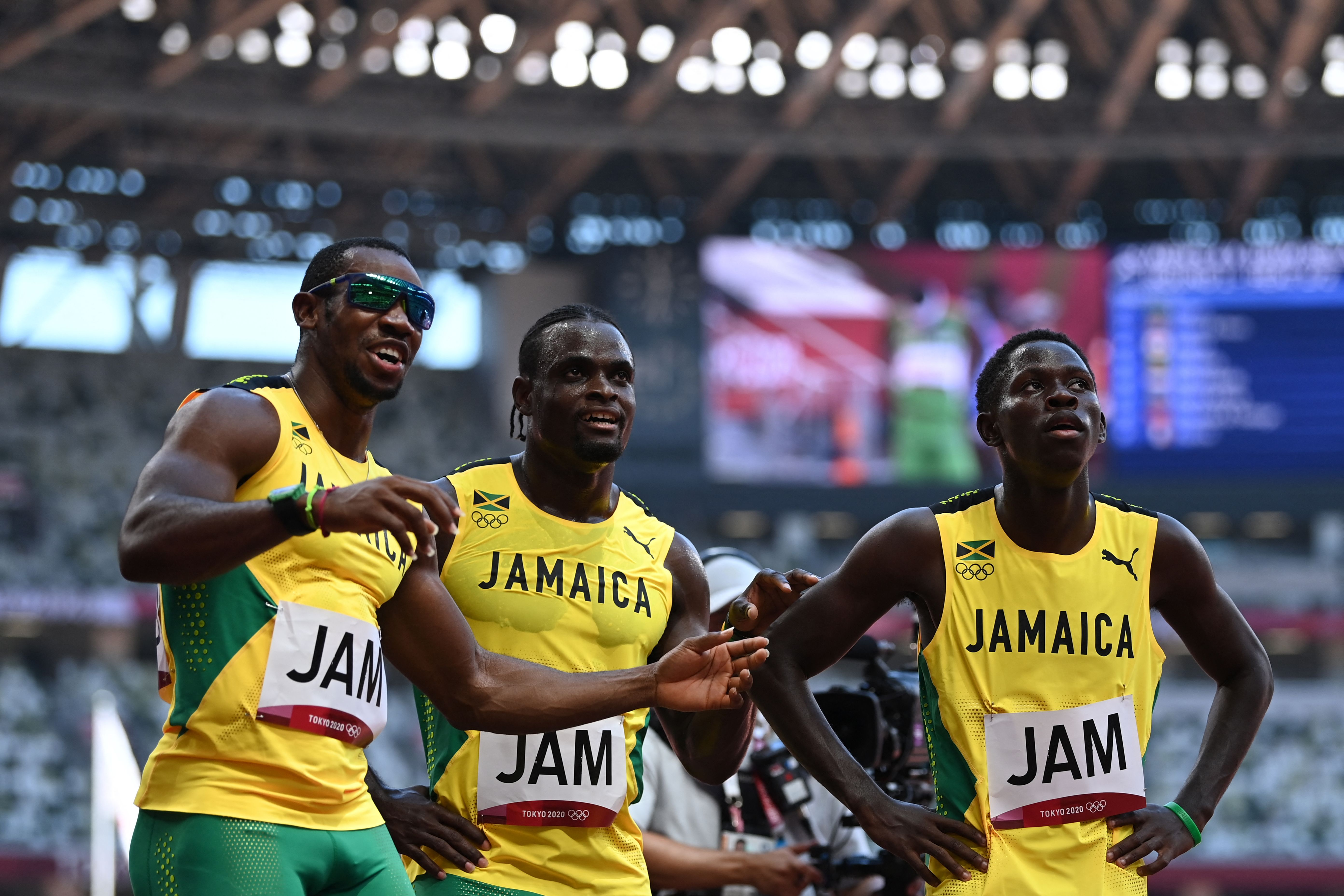 (From L) Jamaica's Yohan Blake, Jamaica's Jevaughn Minzie and Jamaica's Oblique Seville celebrate after winning in the men's 4x100m relay heats during the Tokyo 2020 Olympic Games at the Olympic Stadium in Tokyo on August 5, 2021.