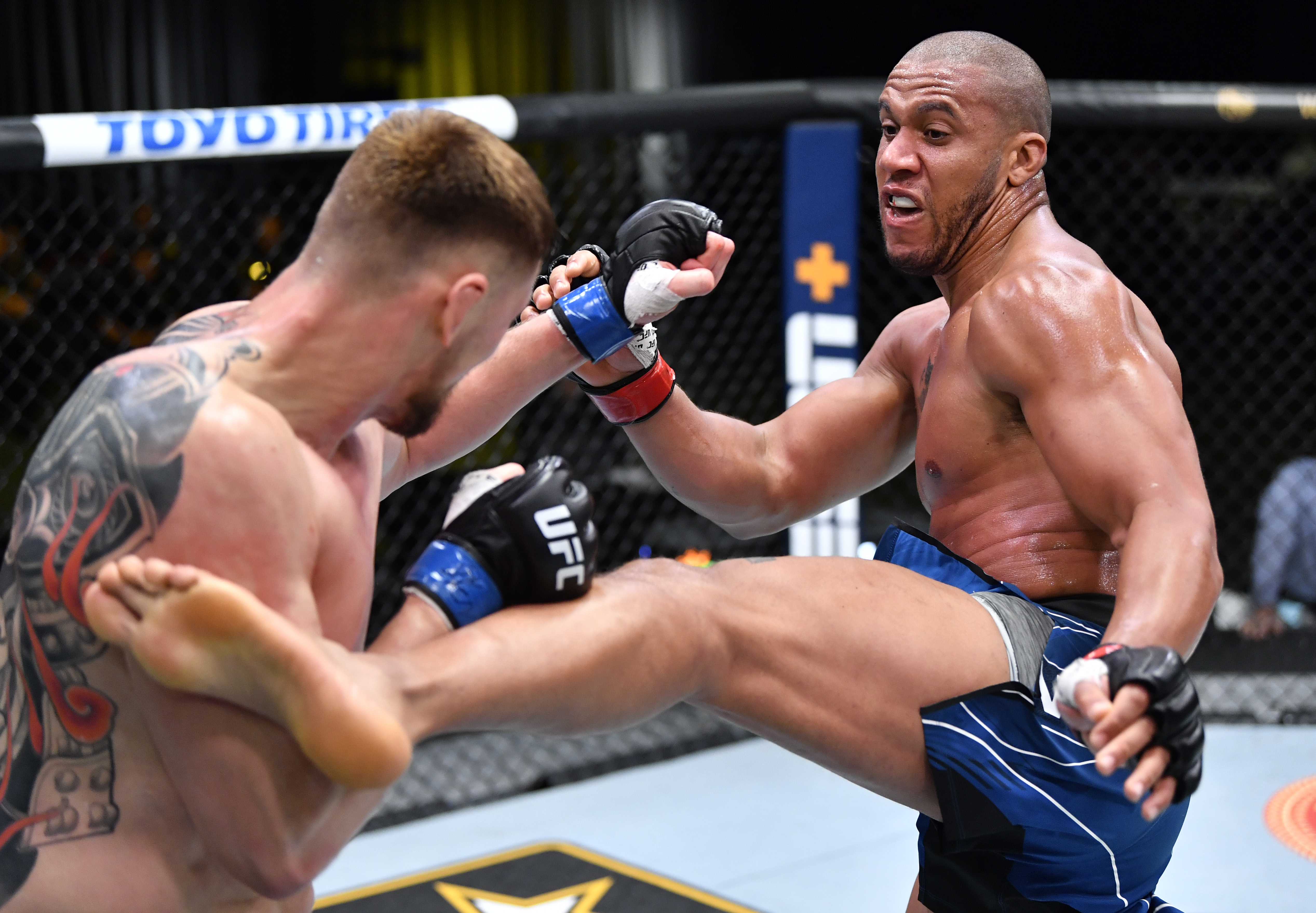 In this handout photo provided by UFC, (R-L) Ciryl Gane of France kicks Alexander Volkov of Russia in a heavyweight fight during the UFC Fight Night event at UFC APEX on June 26, 2021 in Las Vegas, Nevada.