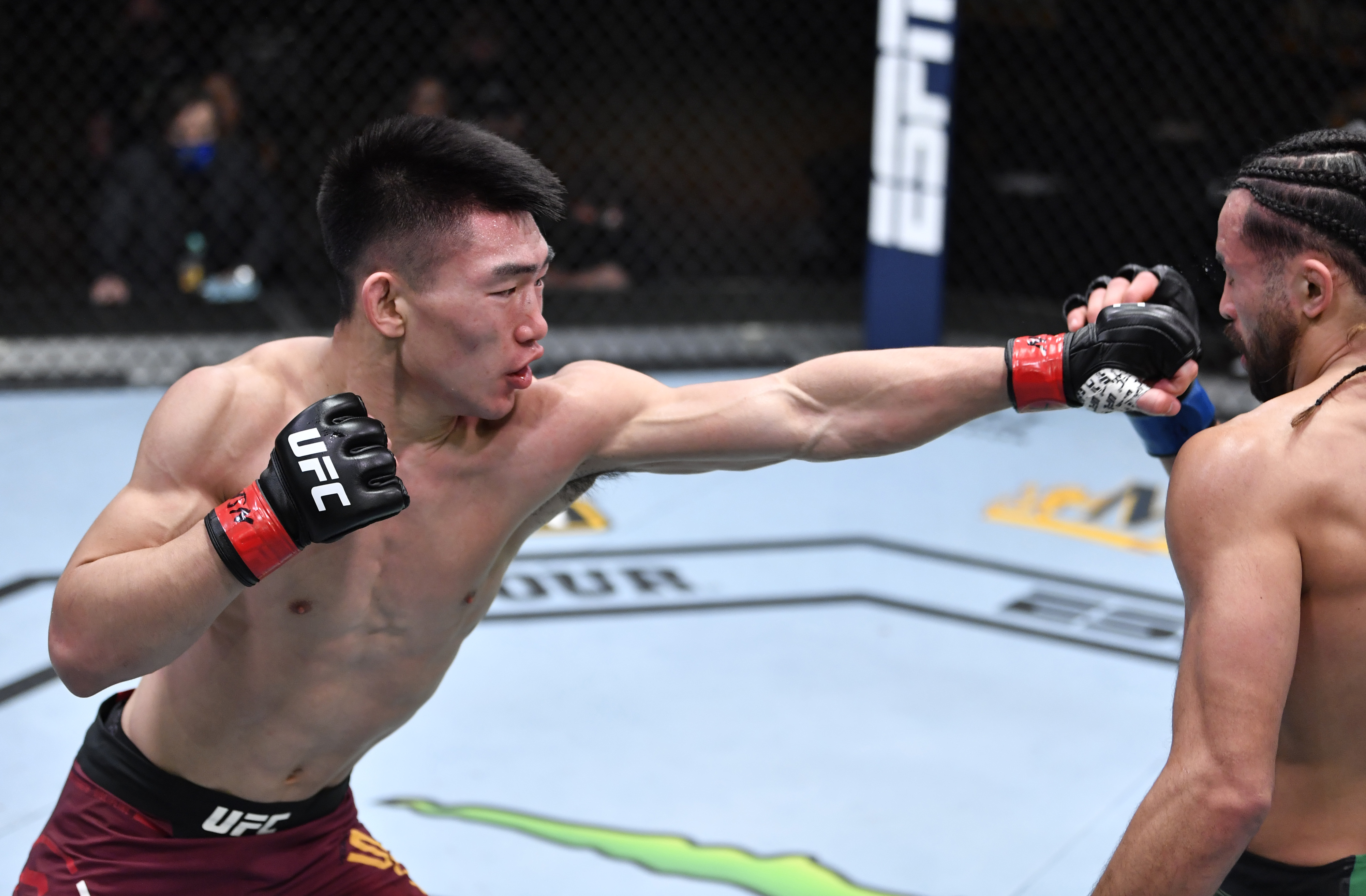 (L-R) Song Yadong of China punches Kyler Phillips in their bantamweight fight during the UFC 259 event at UFC APEX on March 06, 2021 in Las Vegas, Nevada.