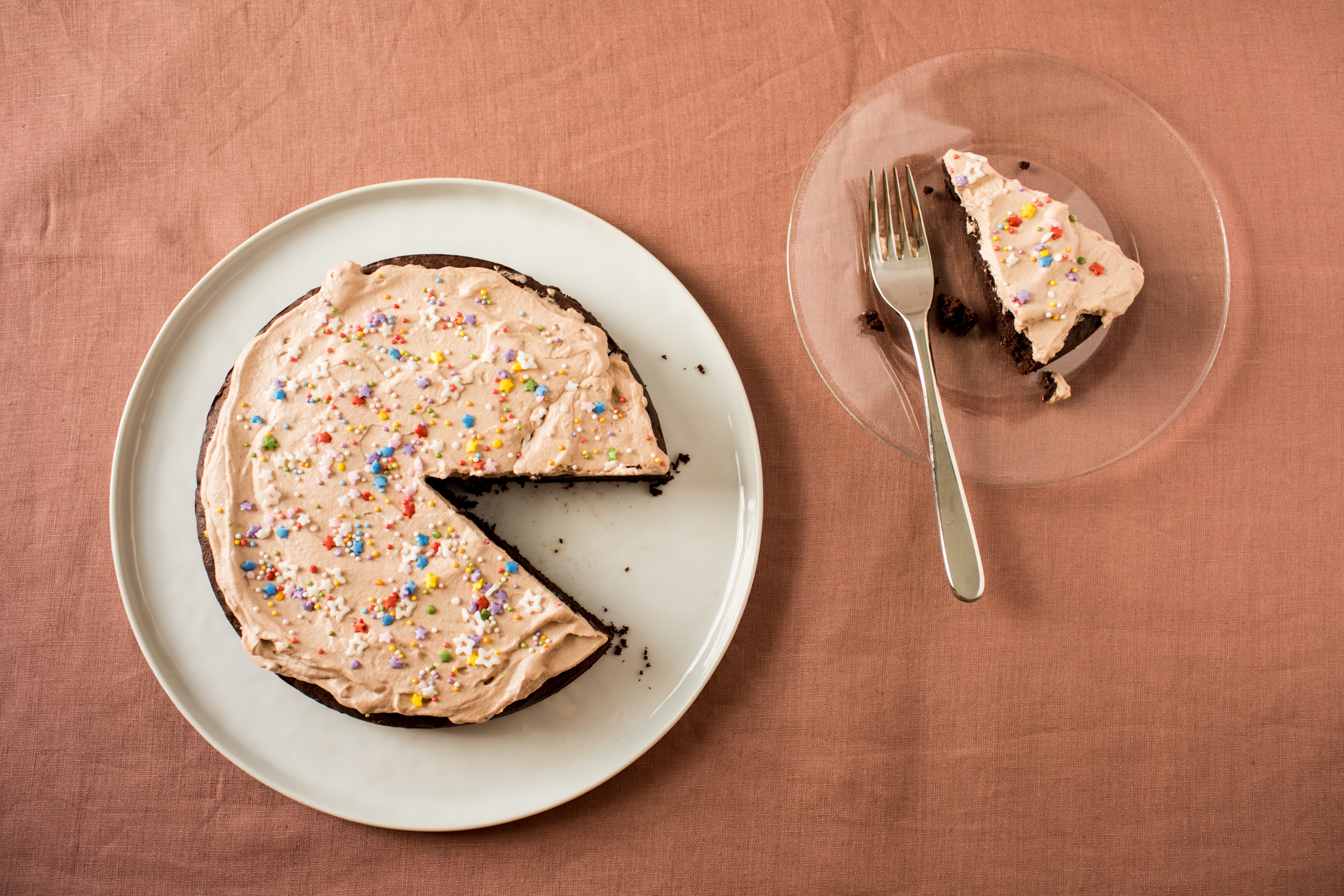 Circular chocolate cake with a light brown whipped cream and sprinkles on top, one triangle has been cut out and is on a separate plate.