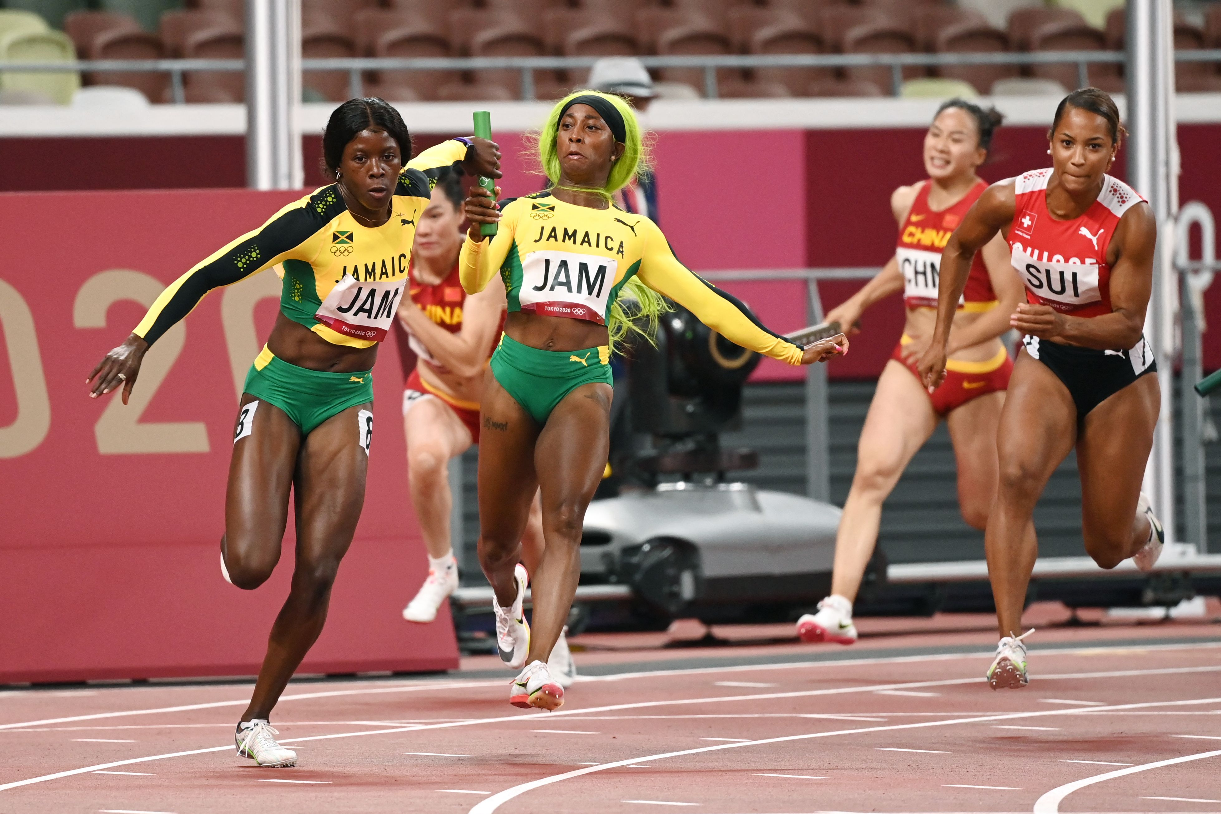 Jamaica's Shelly-Ann Fraser-Pryce (R) passes the baton to Jamaica's Shericka Jackson during the women's 4x100m relay final during the Tokyo 2020 Olympic Games at the Olympic Stadium in Tokyo on August 6, 2021.