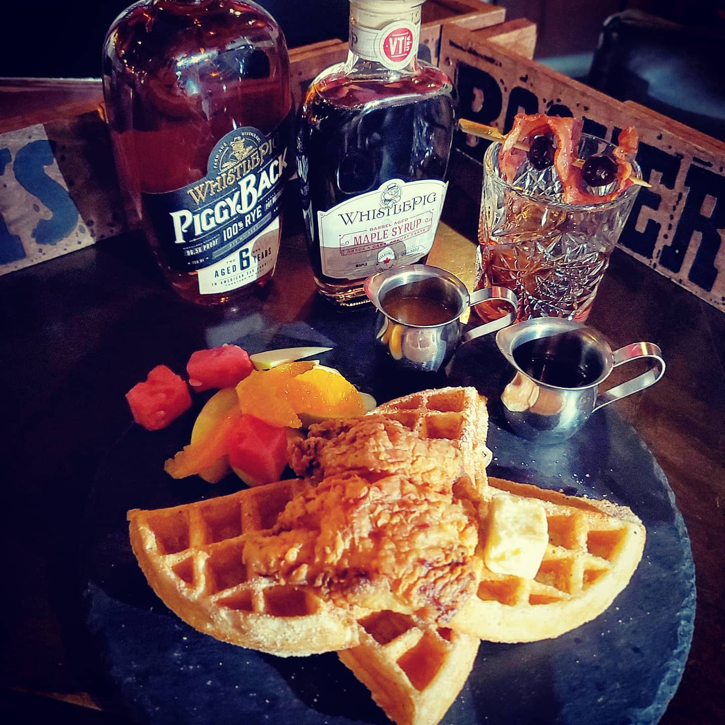 A plate of waffles with chicken with bottles of whiskey behind it