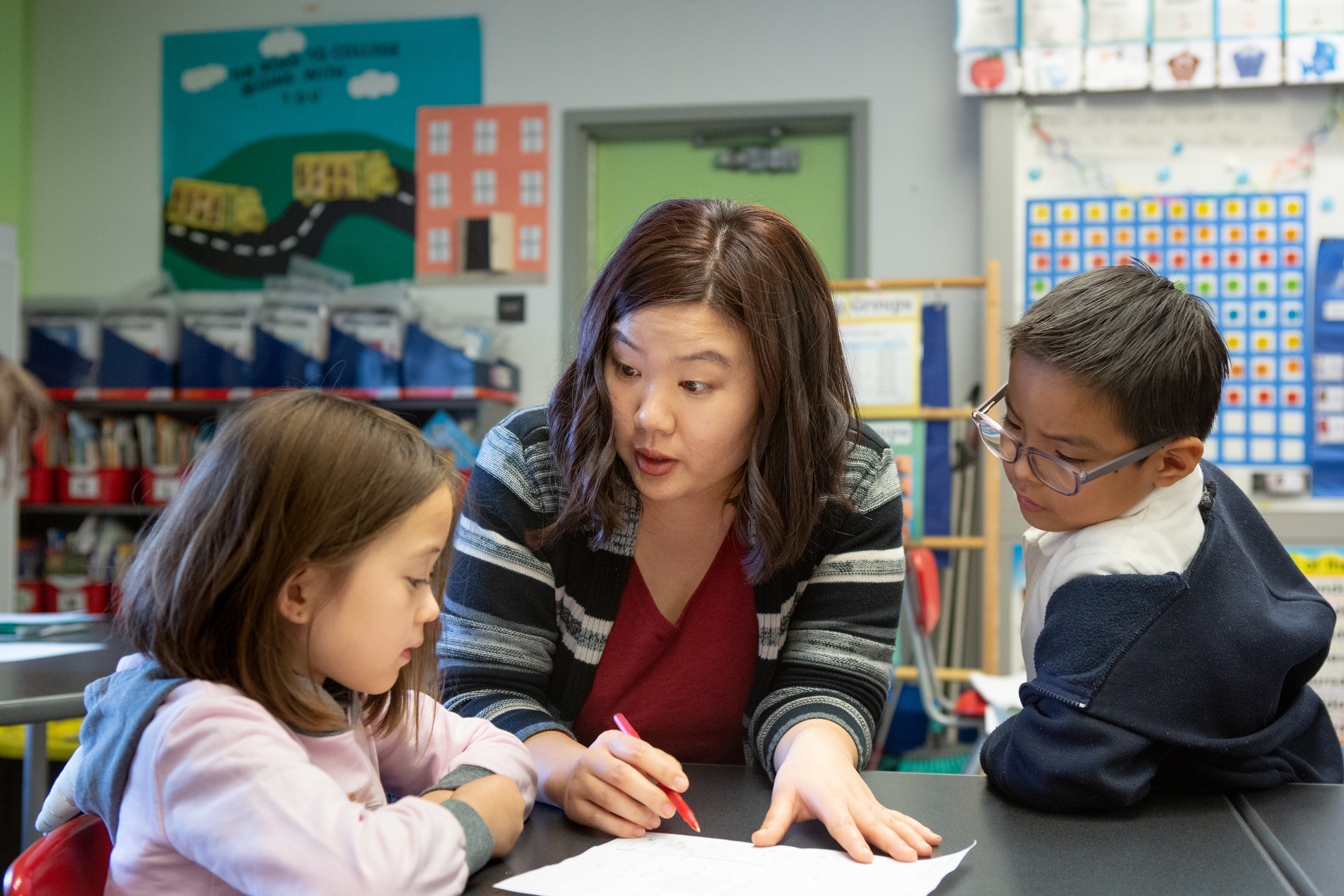 A kindergarten teacher helps a girl and boy with a class activity.