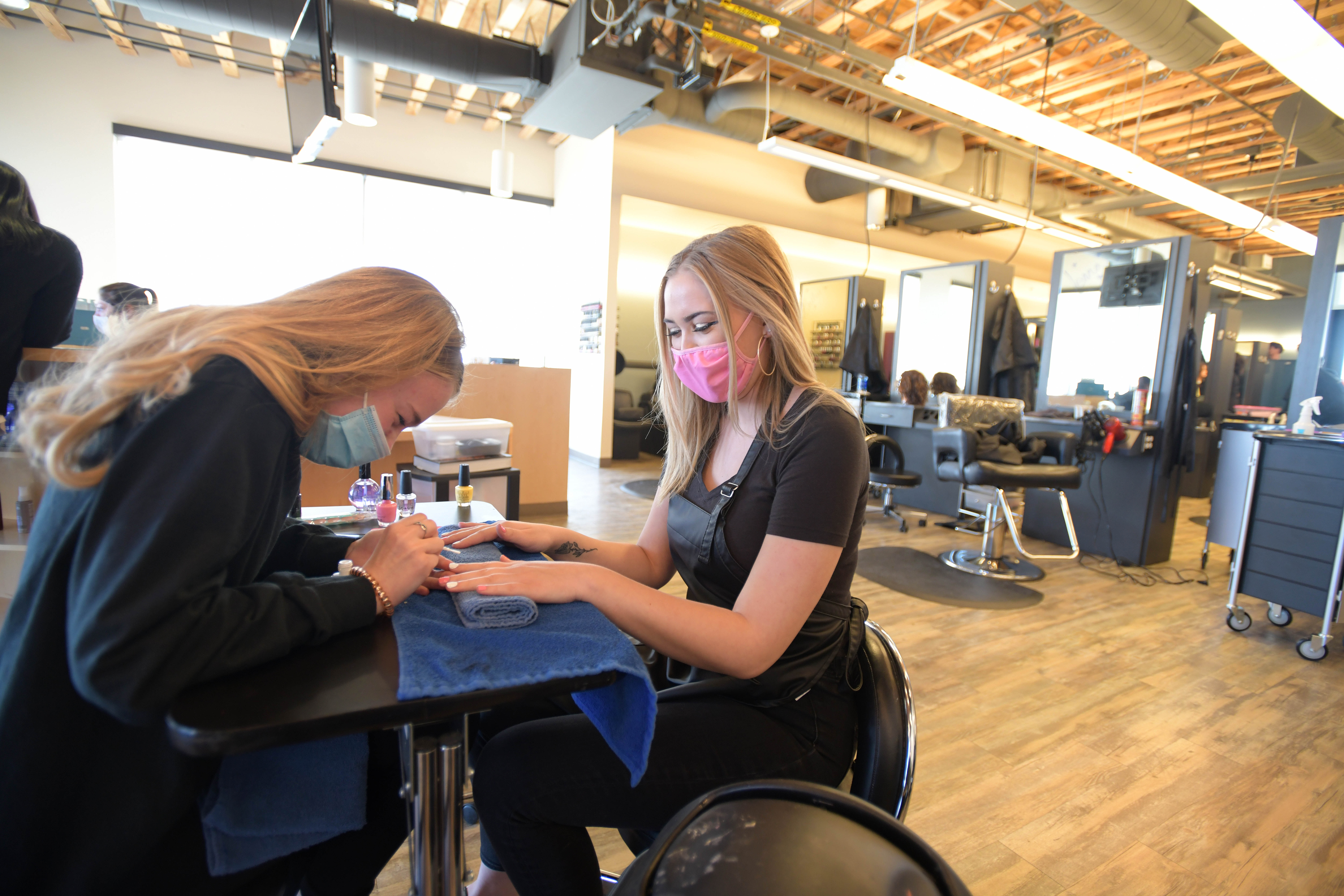 A blonde woman wearing a blue surgical mask paints the nails of another woman who's wearing a pink mask. They are sitting at a table.