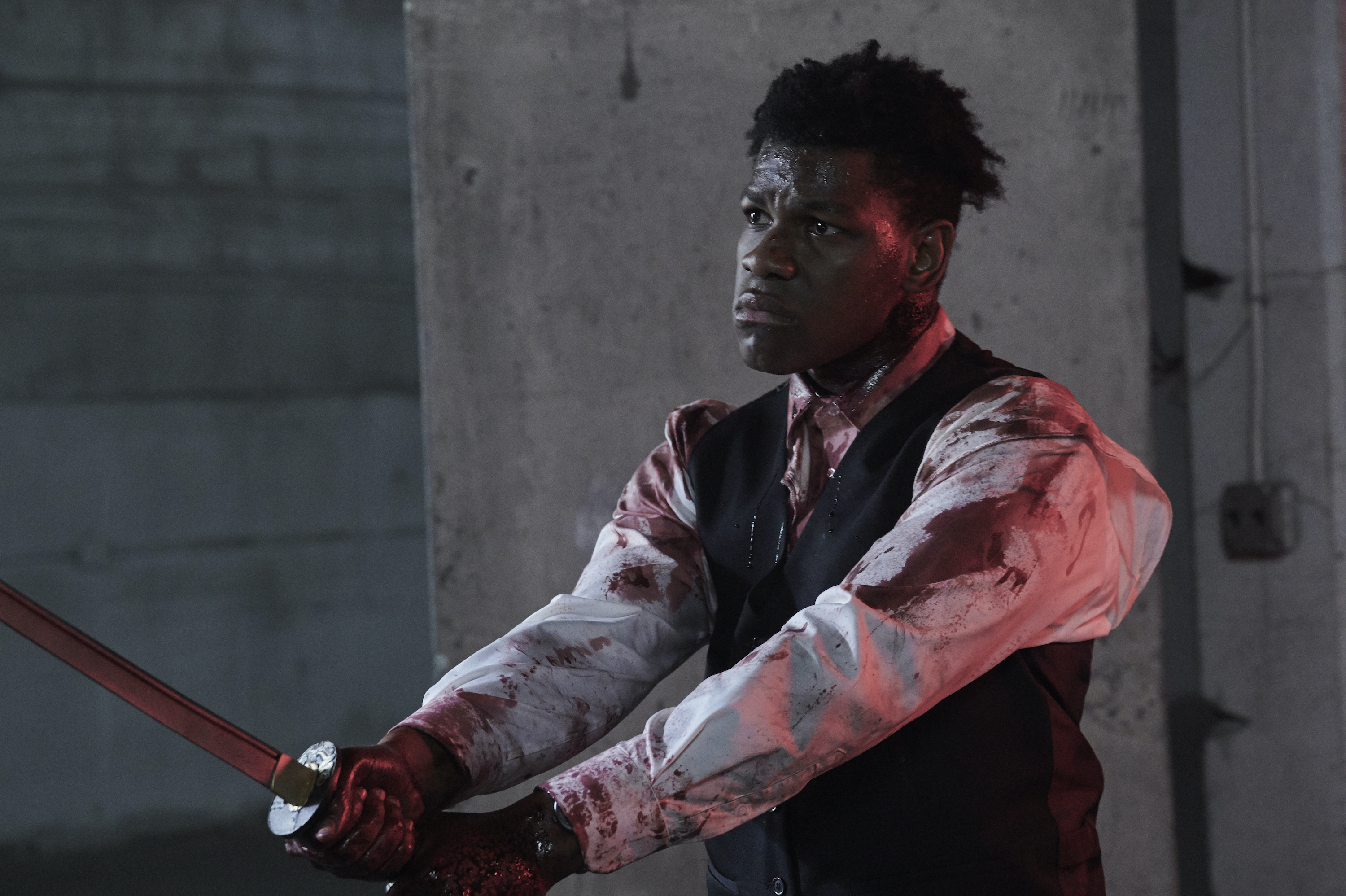 A blood-covered John Boyega looks oddly solemn while wielding a katana