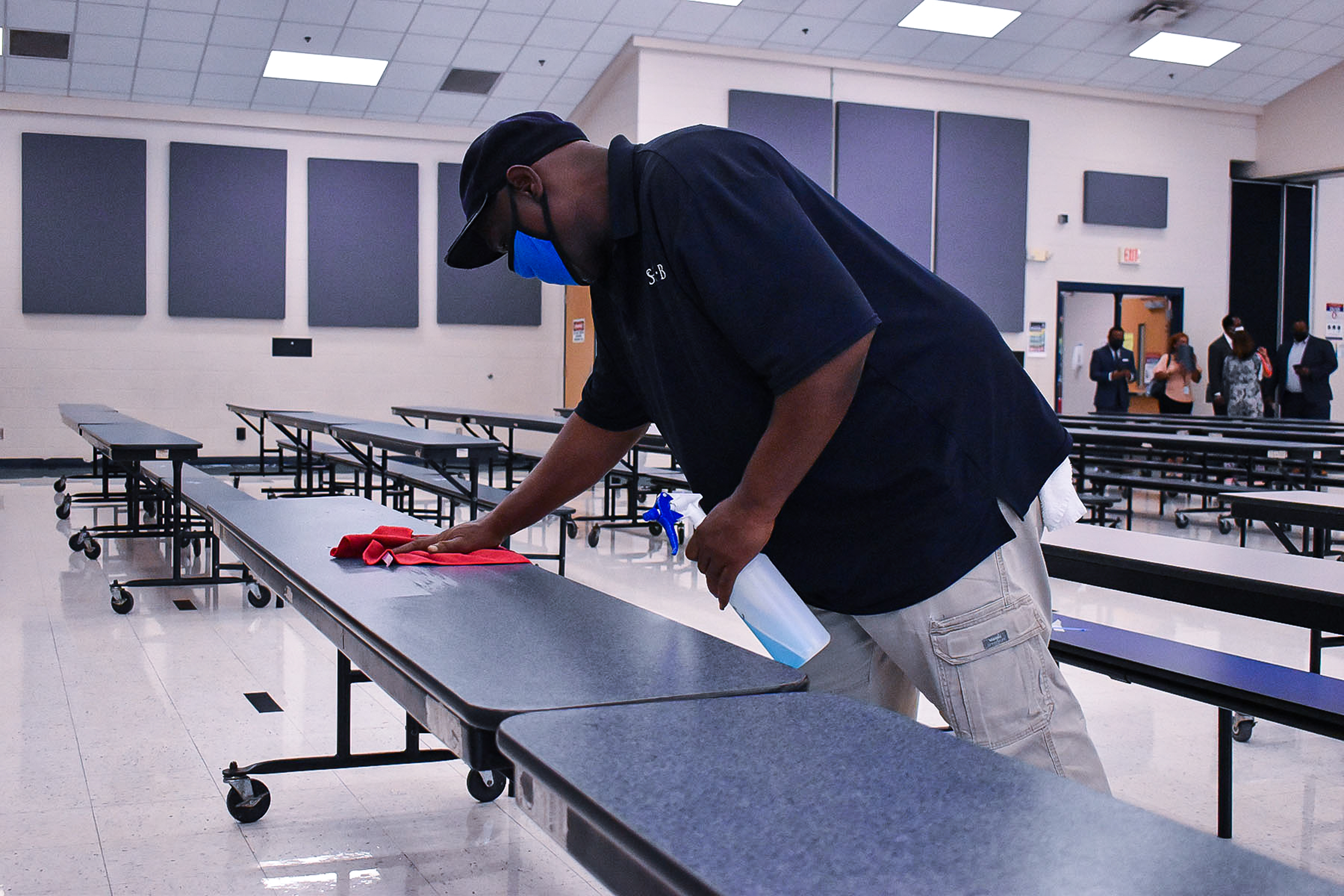 A Shelby County Schools employee sanitizes one of many long cafeteria tables while a group of people stand toward the back of the room.
