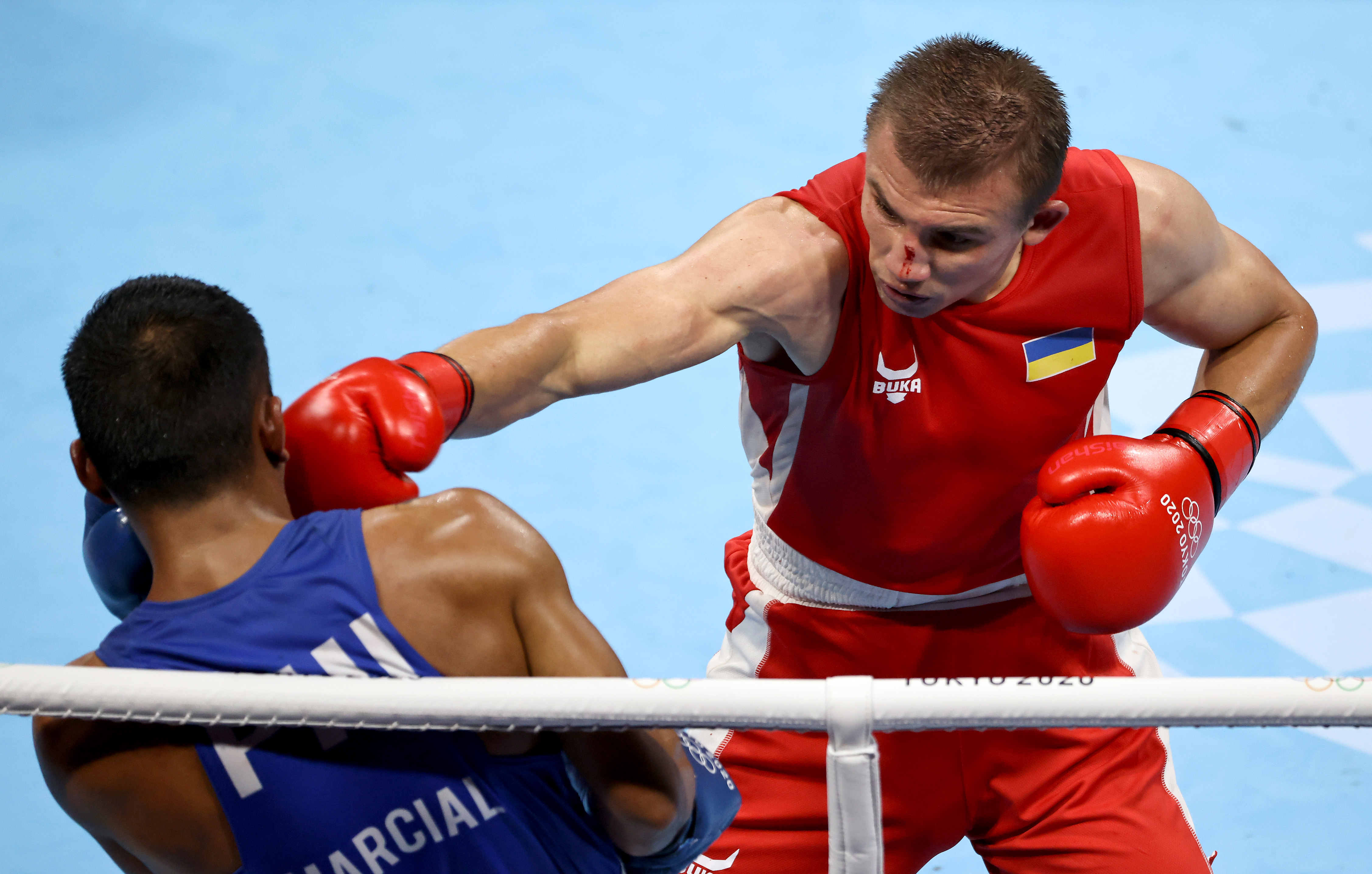 Oleksandr Khyzhniak (red) of Team Ukraine exchanges punches with Eumir Marcial of Team Philippines during the Men's Middle (69-75kg) semi final on day thirteen of the Tokyo 2020 Olympic Games at Kokugikan Arena on August 05, 2021 in Tokyo, Japan.