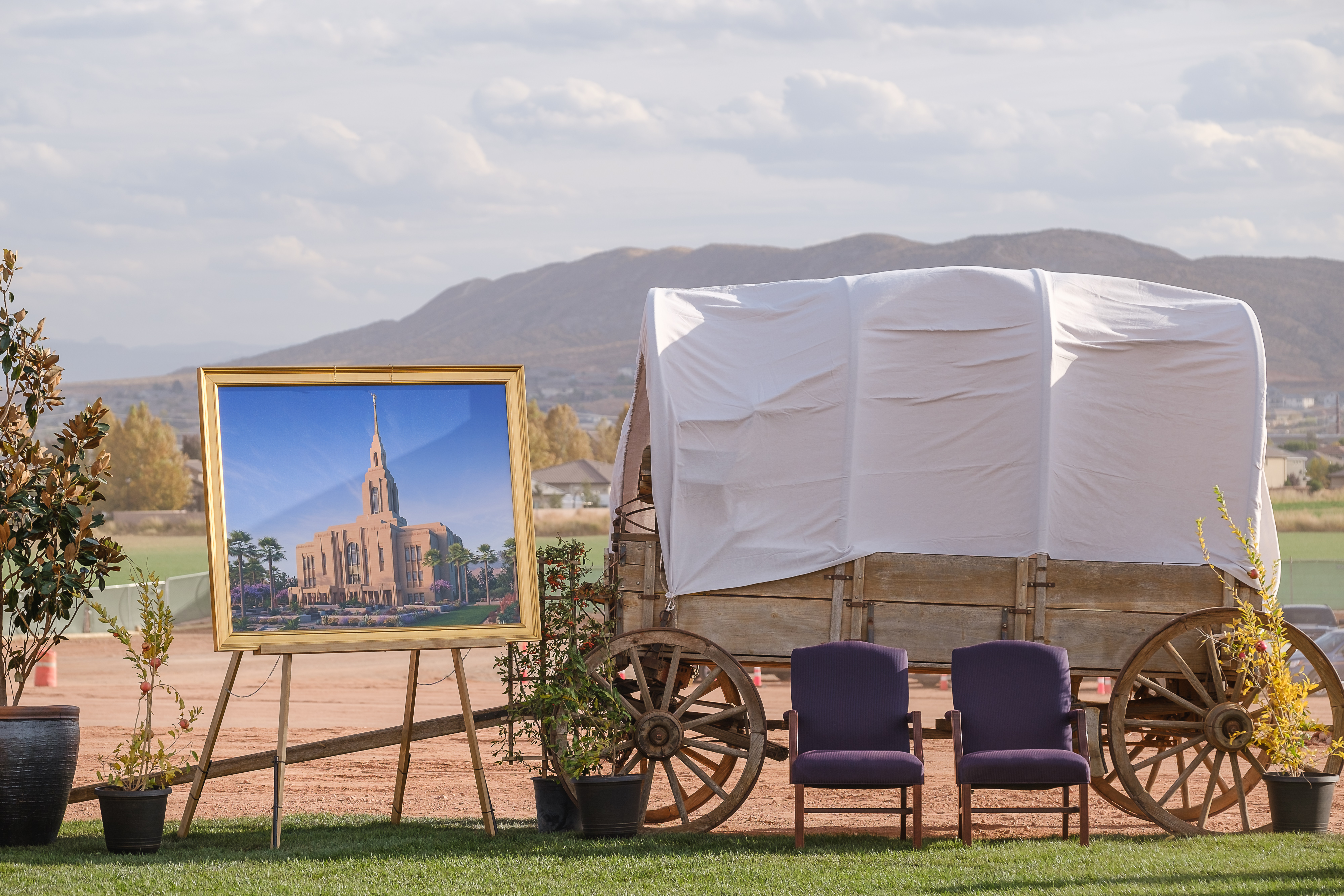 A covered wagon and a rendering of the Red Cliffs Utah Temple of The Church of Jesus Christ of Latter-day Saints.