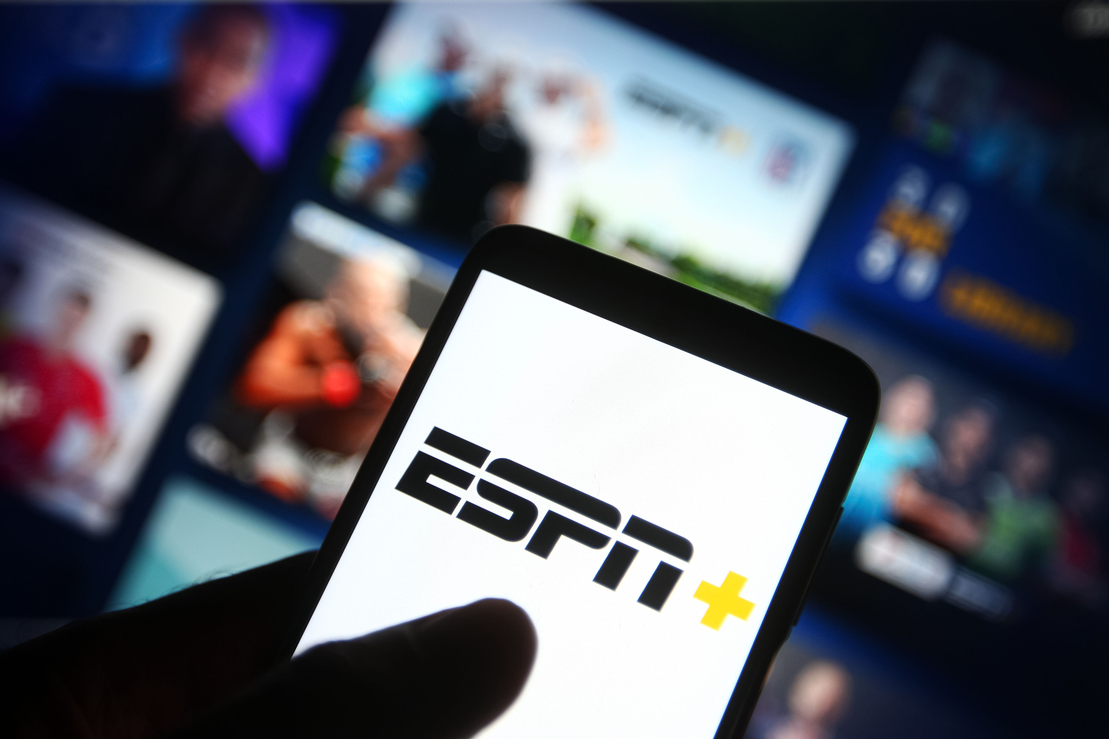In this photo illustration the ESPN+ (ESPN Plus) logo of an US video streaming service is seen on a smartphone with its website in the background.
