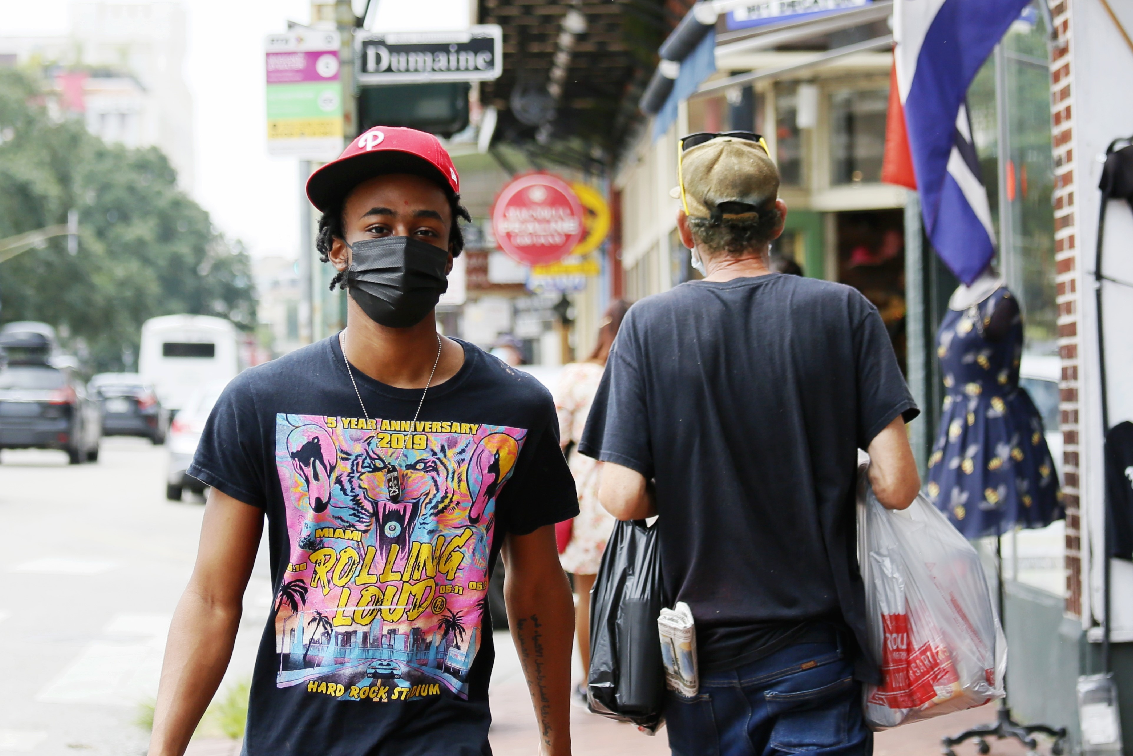 A young black man wearing a black face mask and a red hat walks along a busy New Orleans street, with retail displays on the sidewalk and passersby behind him.