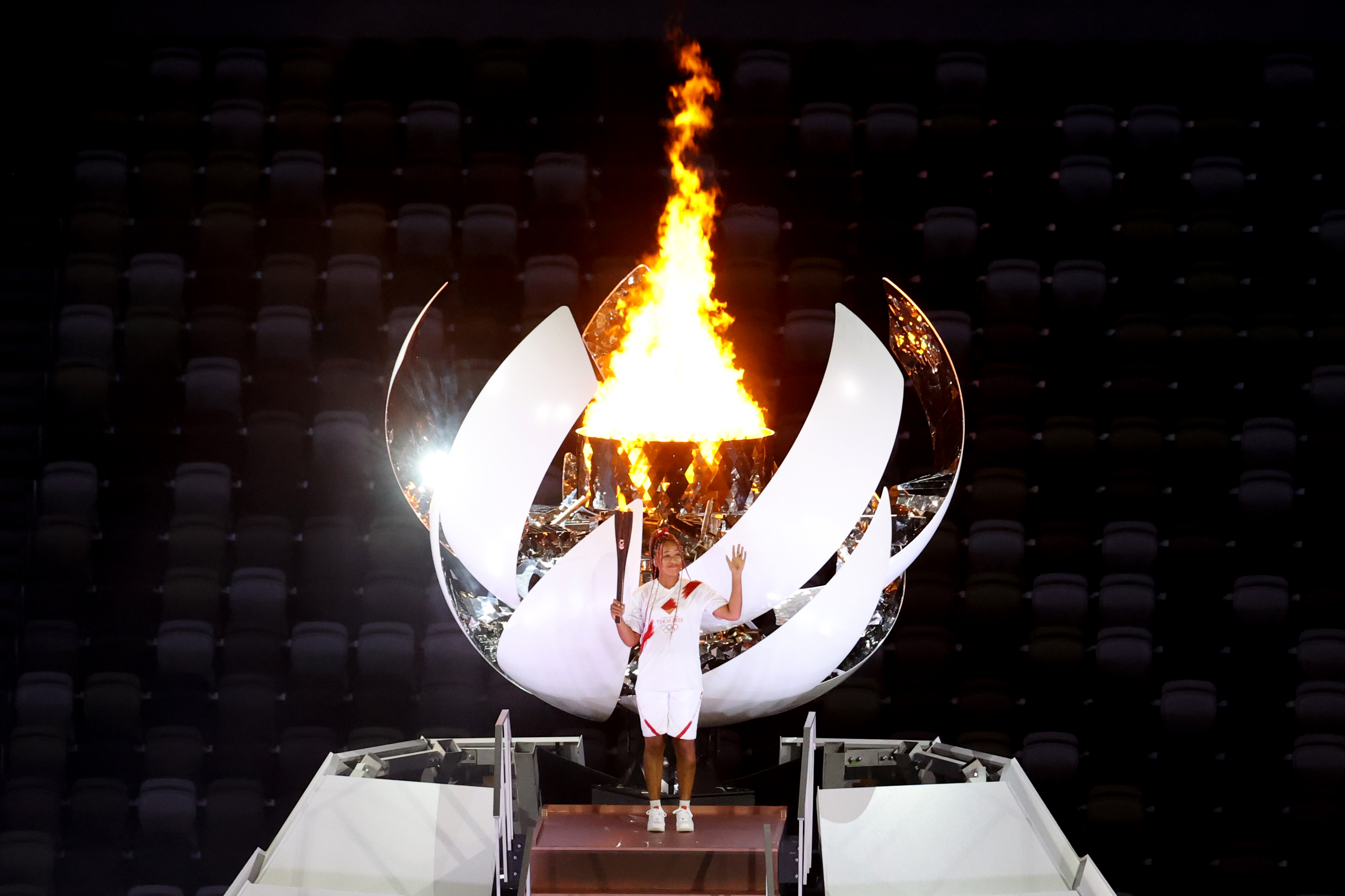 Naomi Osaka of Japan stands with the Olympic flame during the Opening Ceremony of the Tokyo 2020 Olympic Games at Olympic Stadium on July 23, 2021 in Tokyo, Japan.