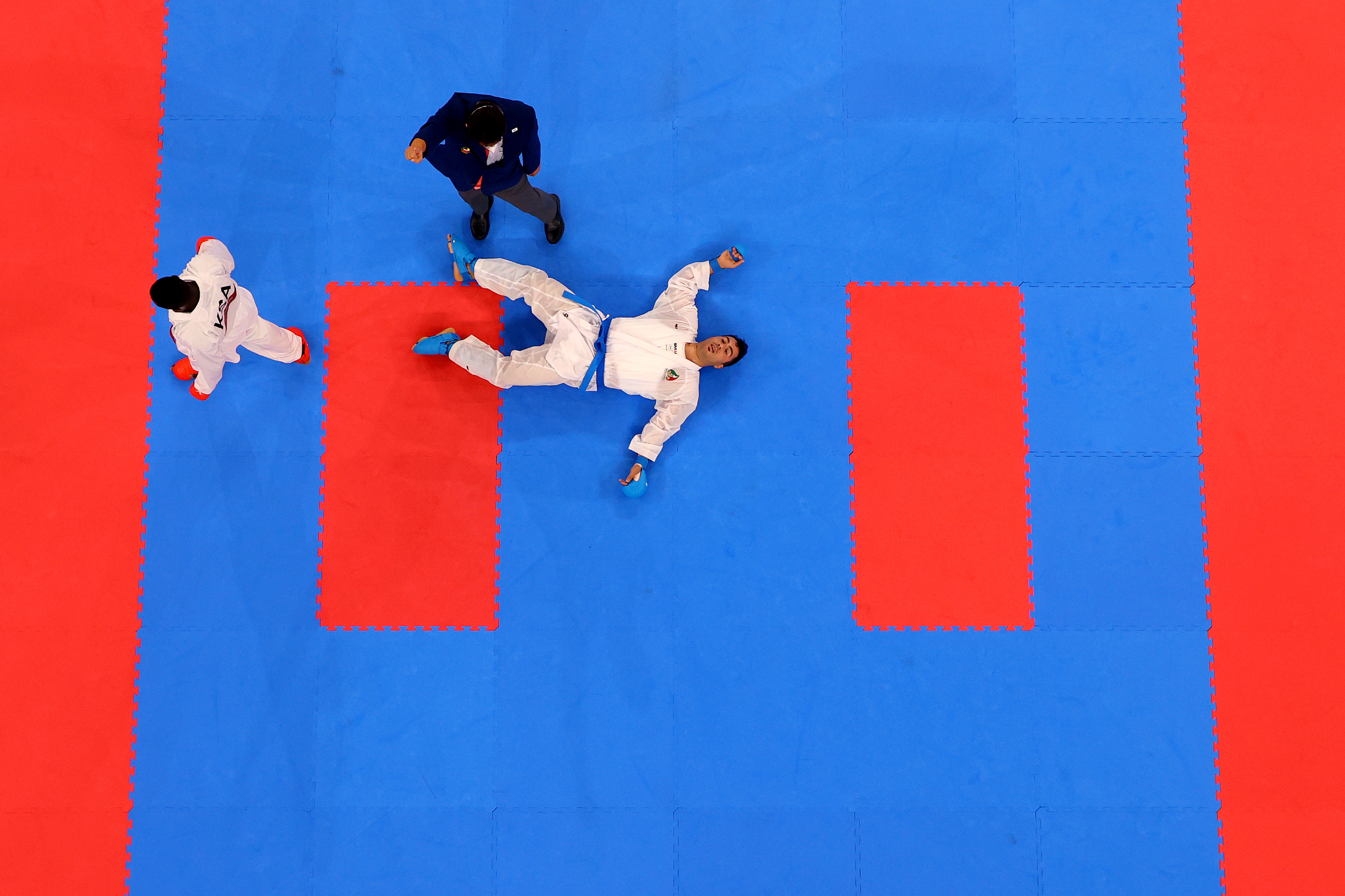 Sajad Ganjzadeh (R) of Team Iran lays on the tatami after being struck by Tareg Hamedi of Team Saudi Arabia during the Men's Karate Kumite +75kg Gold Medal Bout on day fifteen of the Tokyo 2020 Olympic Games at Nippon Budokan on August 07, 2021 in Tokyo, Japan.