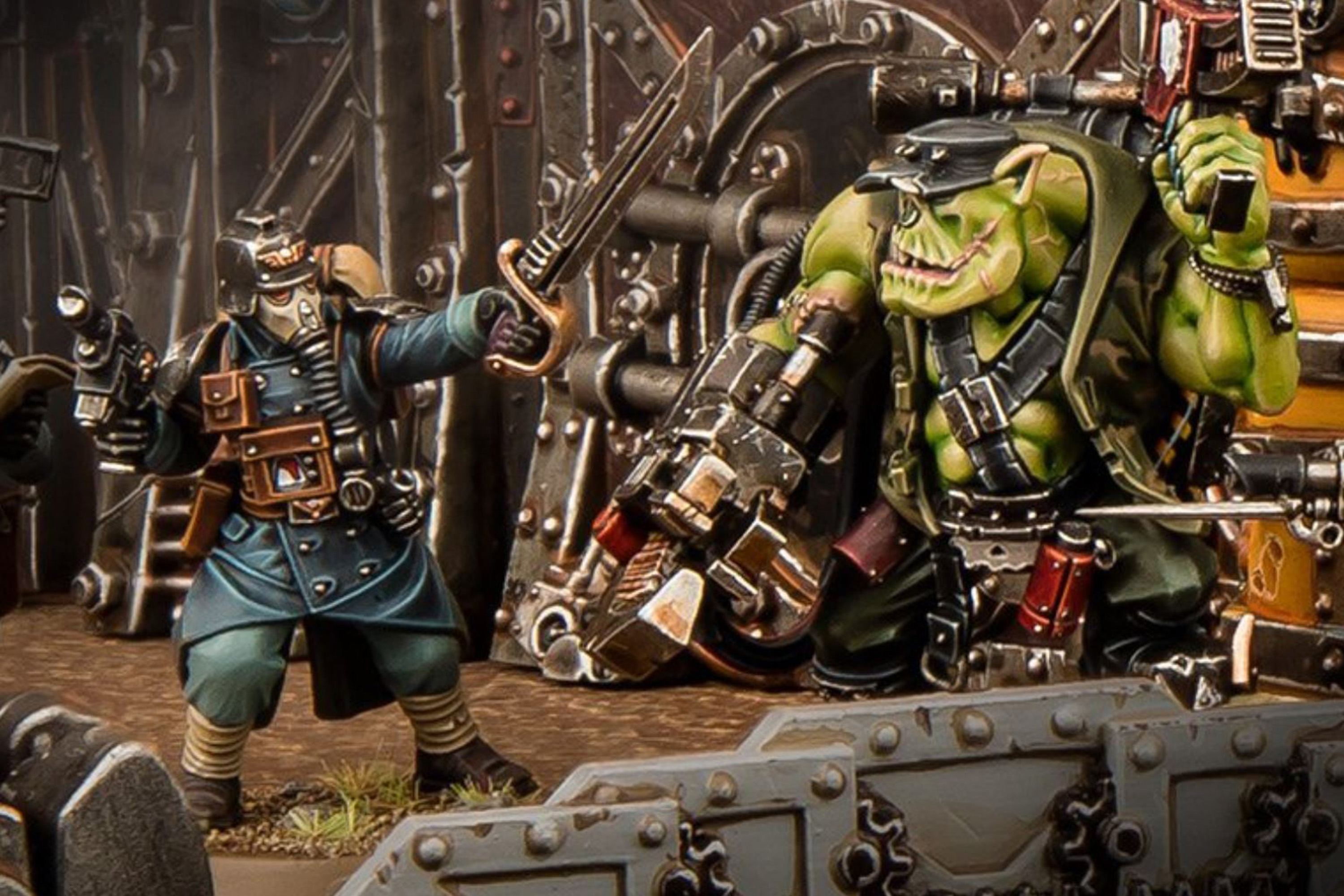A Krieg sergeant in blue squares off against a hulking Ork with a mechanical arm.