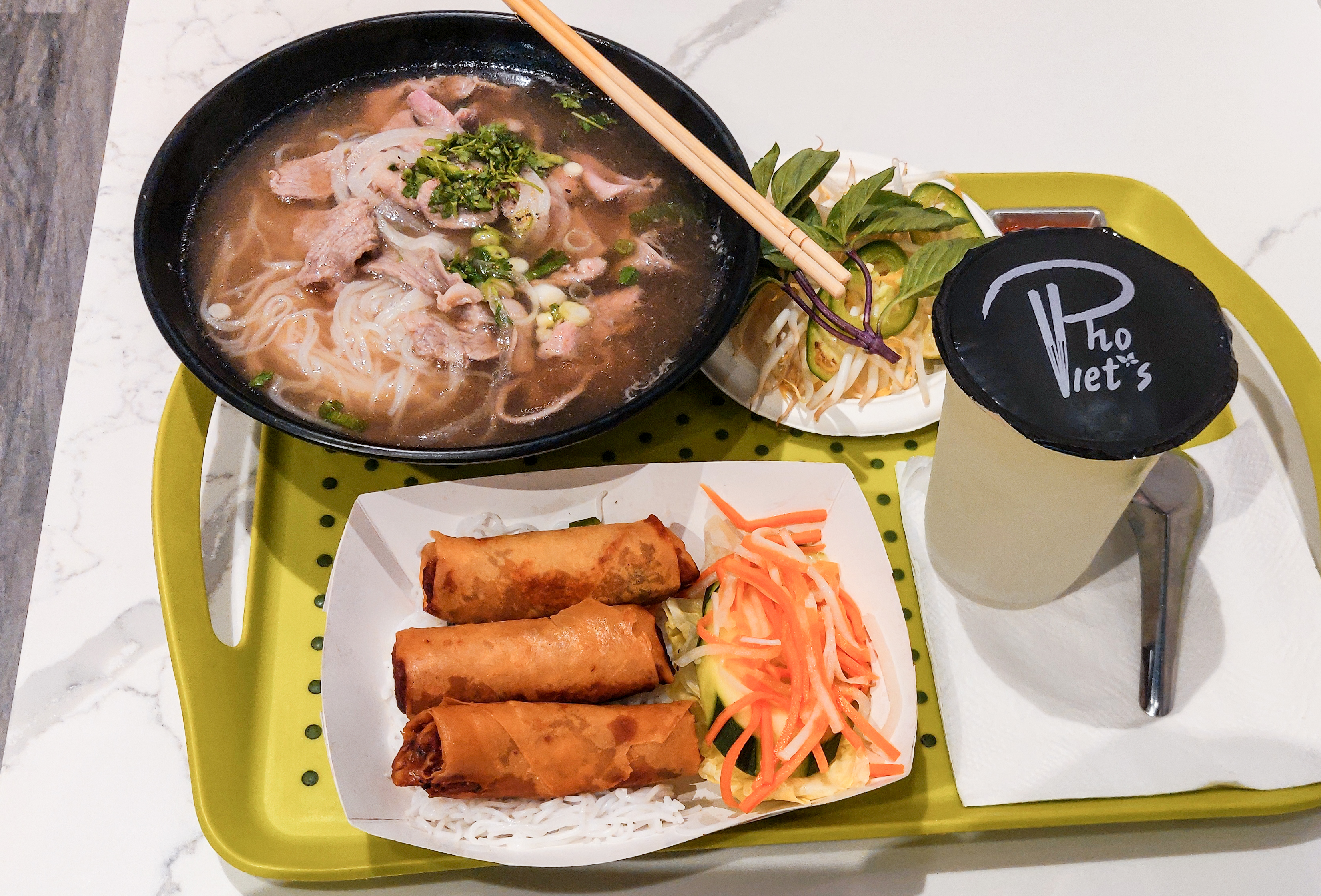 Vietnamese noodle soup, spring rolls, and a plastic cup of lemonade sit on a green tray on a white tabletop. The drink is covered with a black top branded with the logo of the restaurant, Pho Viet's.