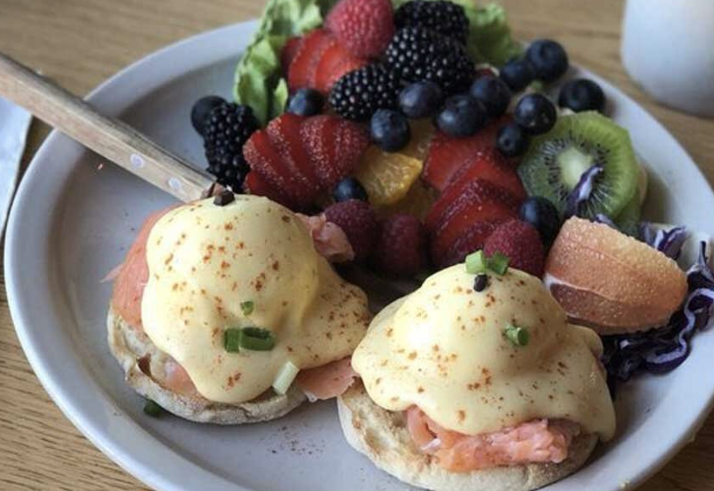 A Salmon Benedict with a side of assorted fruit on a white plate.