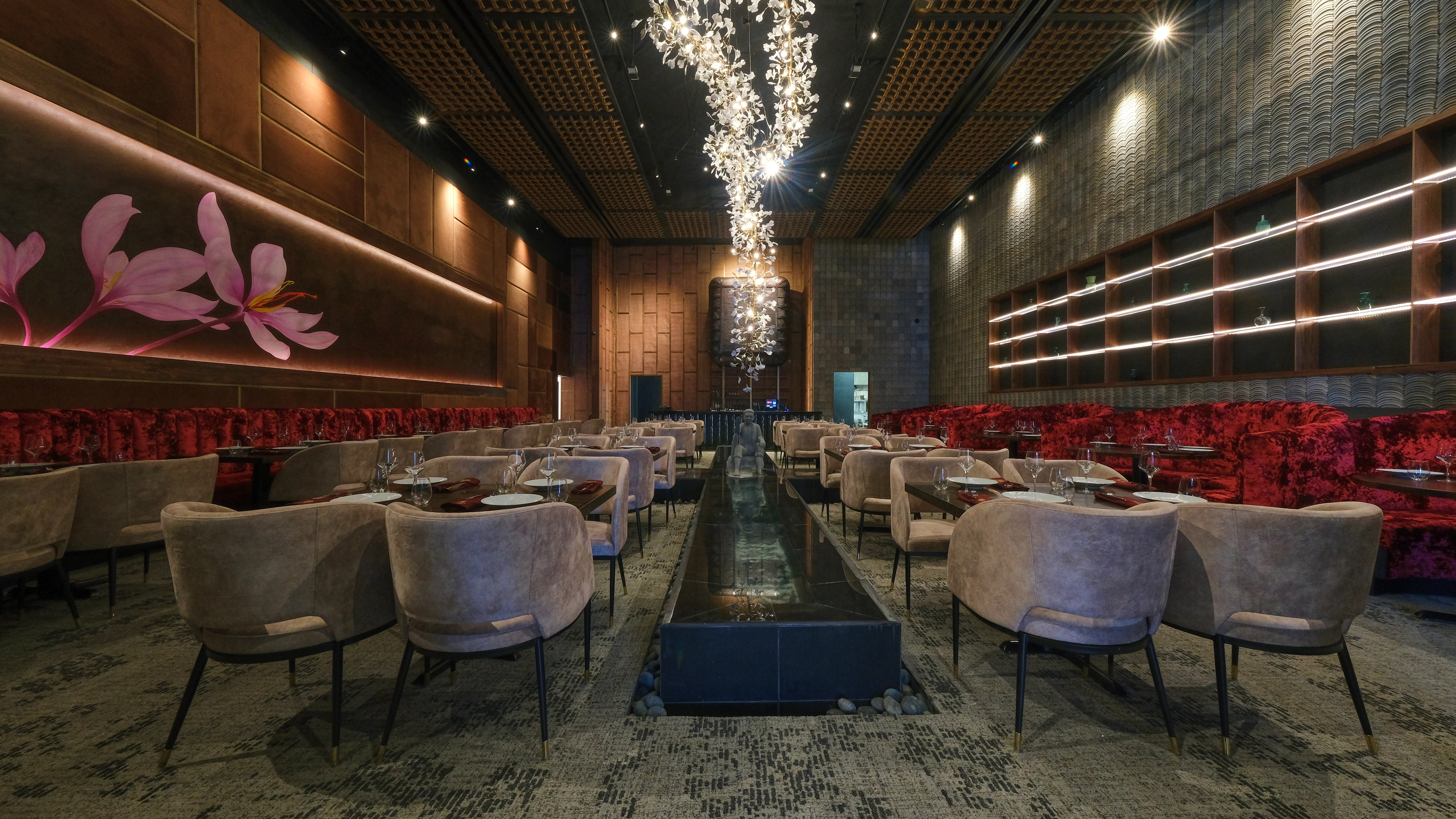 A dark restaurant interior with a white flower light overhead, chairs on the side, and a fountain in the center