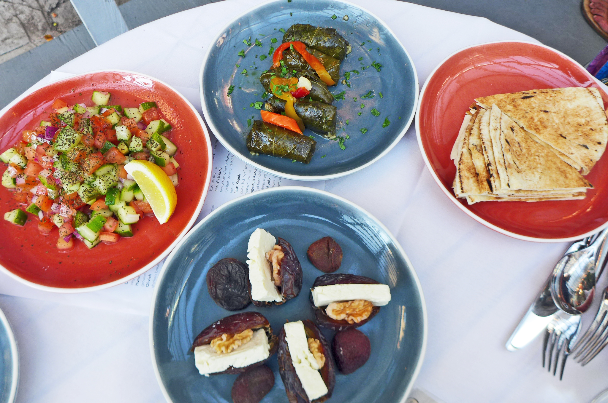 Four small plates in various colors and a pile of cut pitas.